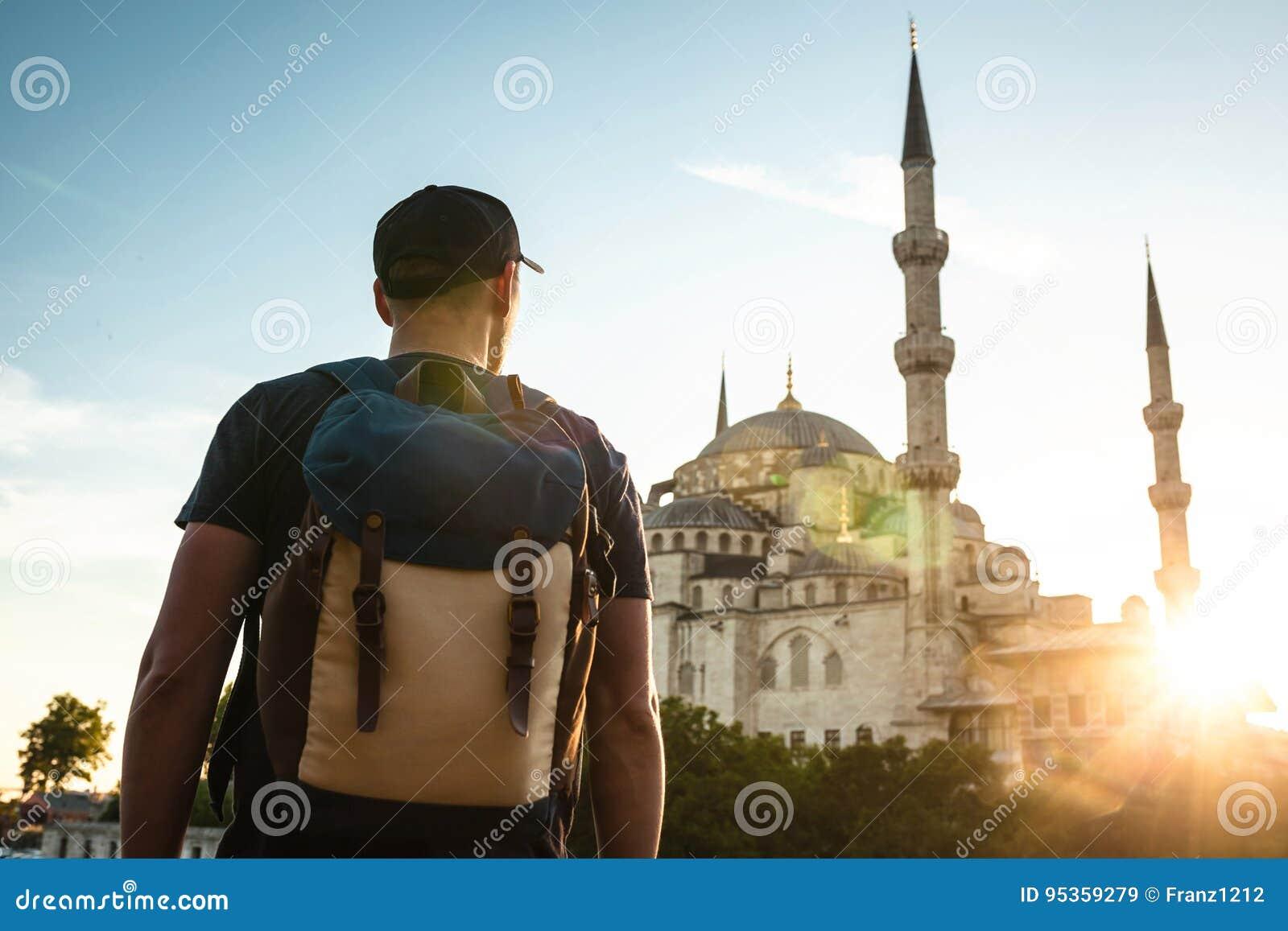 Een mens in een honkbal GLB met een rugzak naast de blauwe moskee is een beroemd gezicht in Istanboel Reis, toerisme