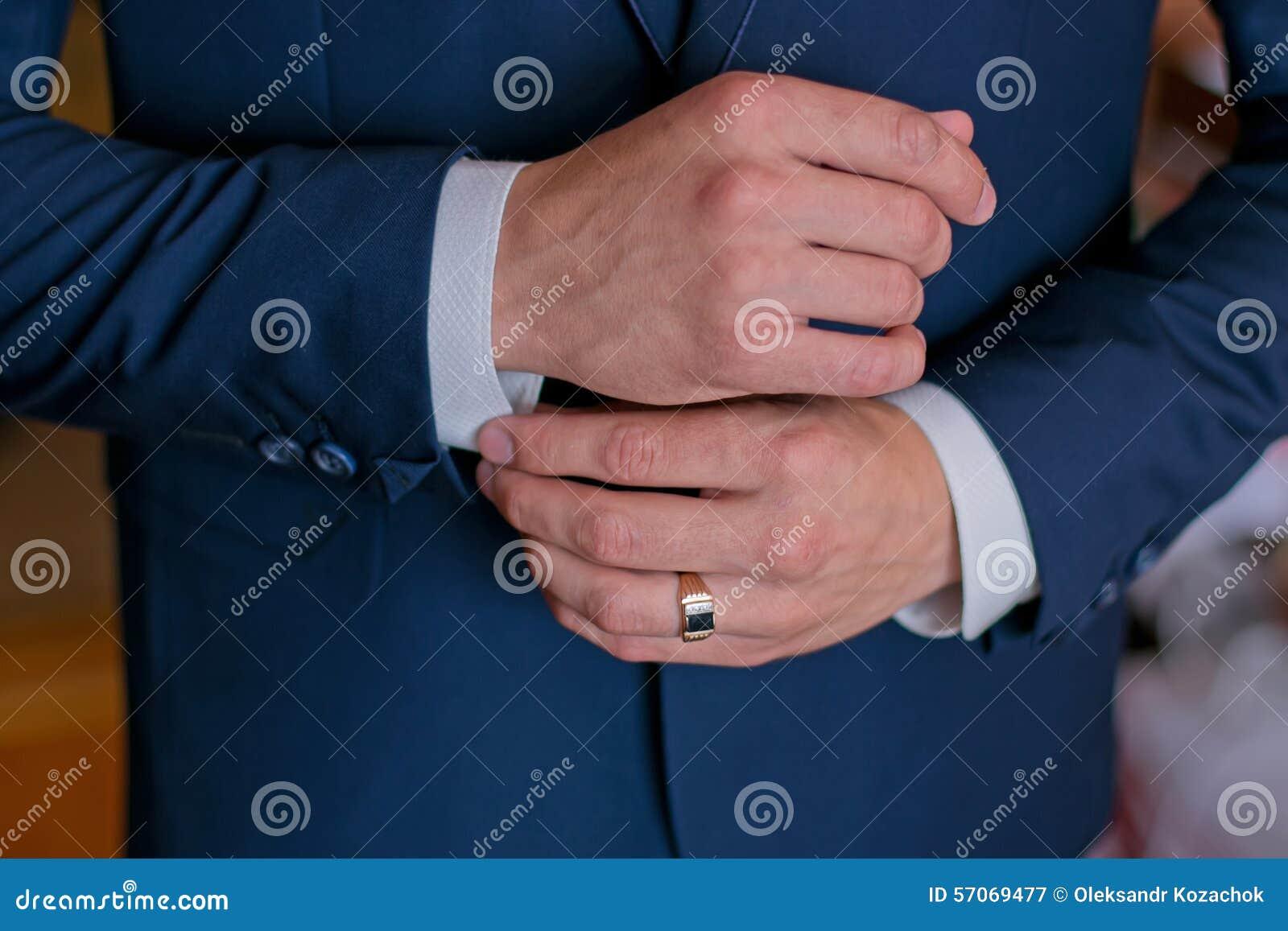 Een mens in een zwart kostuum maakt zijn cufflinks recht