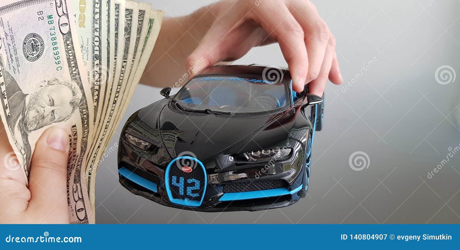 Een mens houdt in van hem indient het stuk speelgoed van het de autometaal van lucht Zwarte Bugatti Chiron terwijl andere persoon