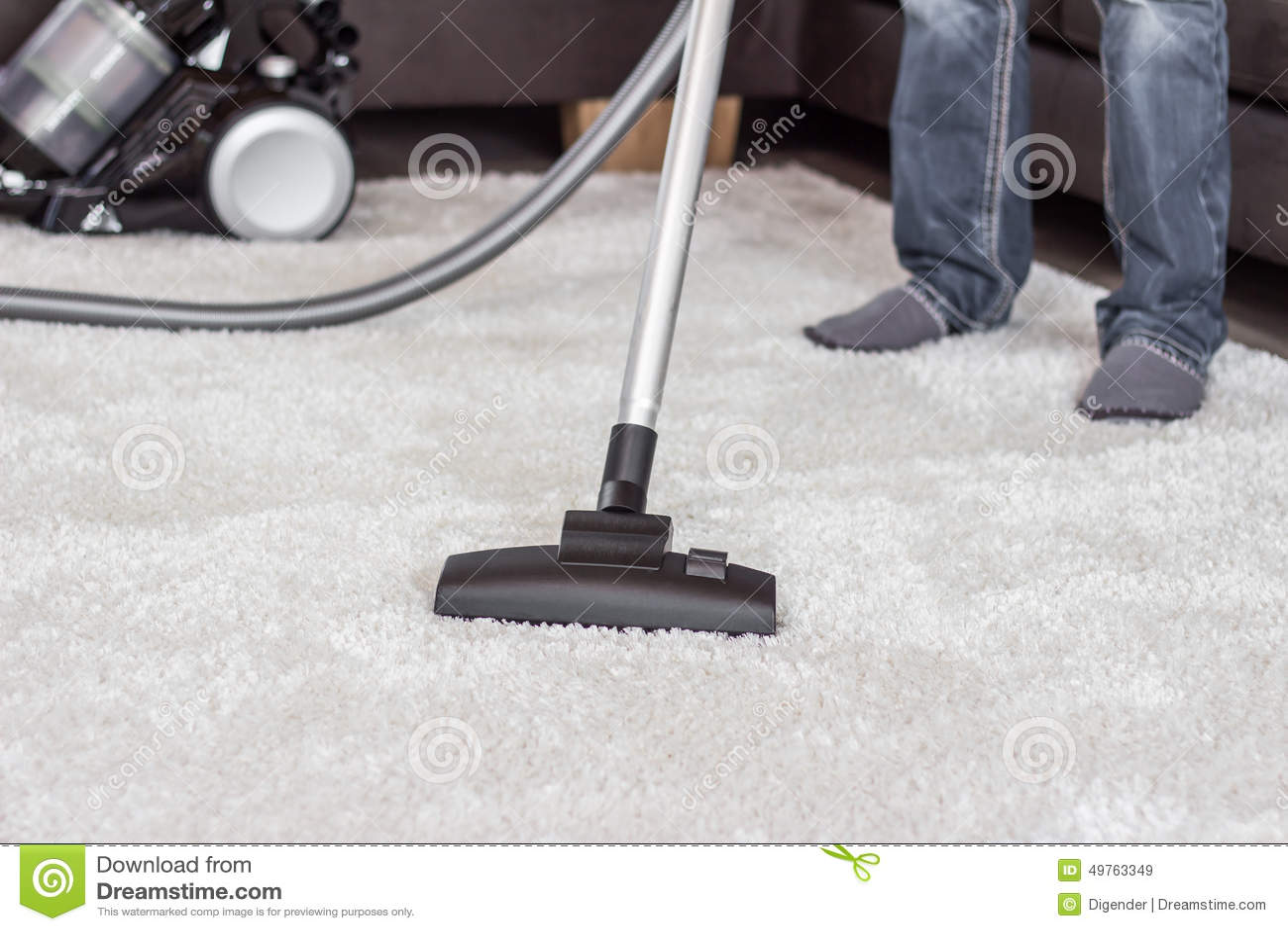 Een mens maakt het tapijt met een stofzuiger schoon
