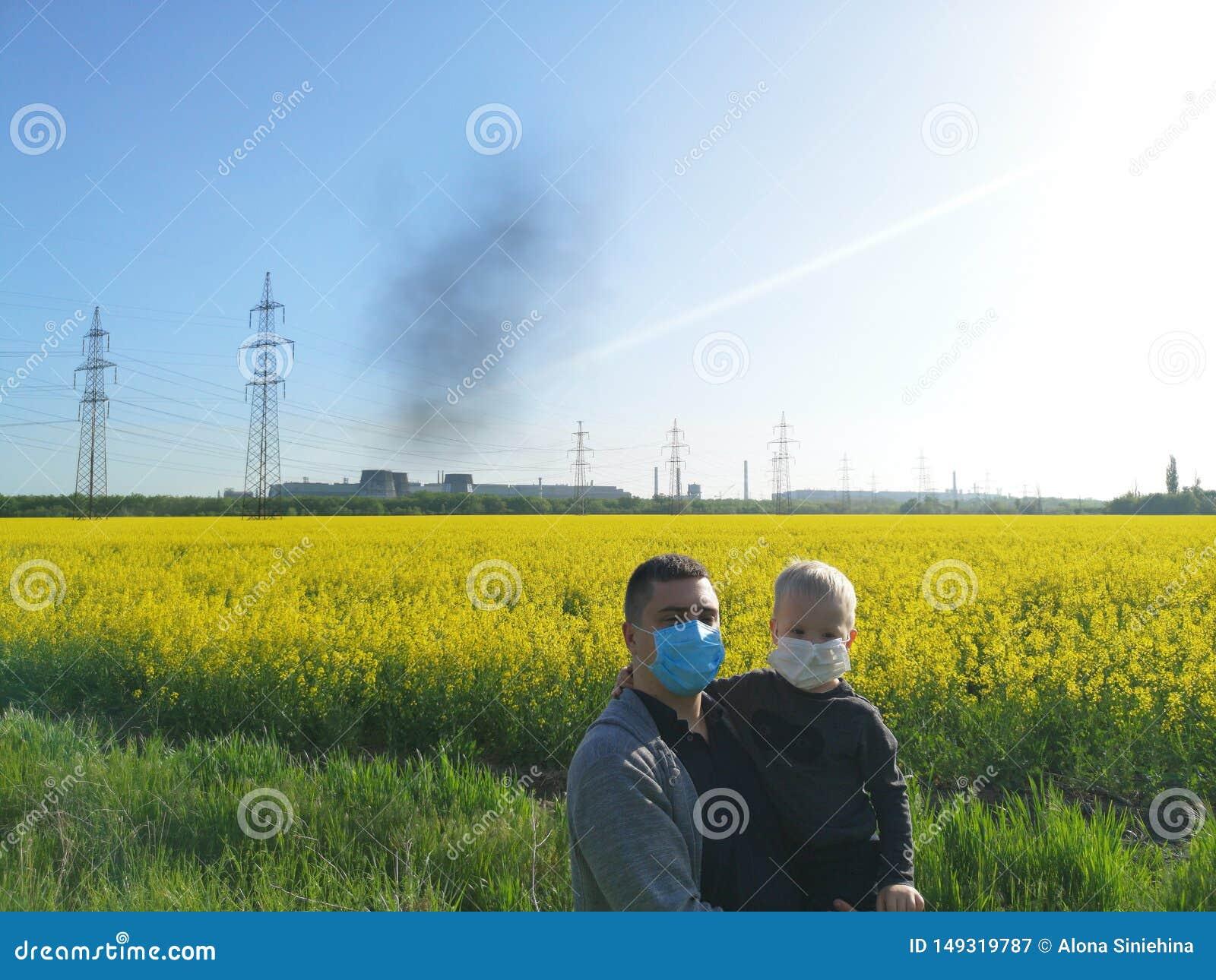 Een mens met een kind in van hem dient medische maskers op de achtergrond van de installatie in Het concept milieuvervuiling, eco