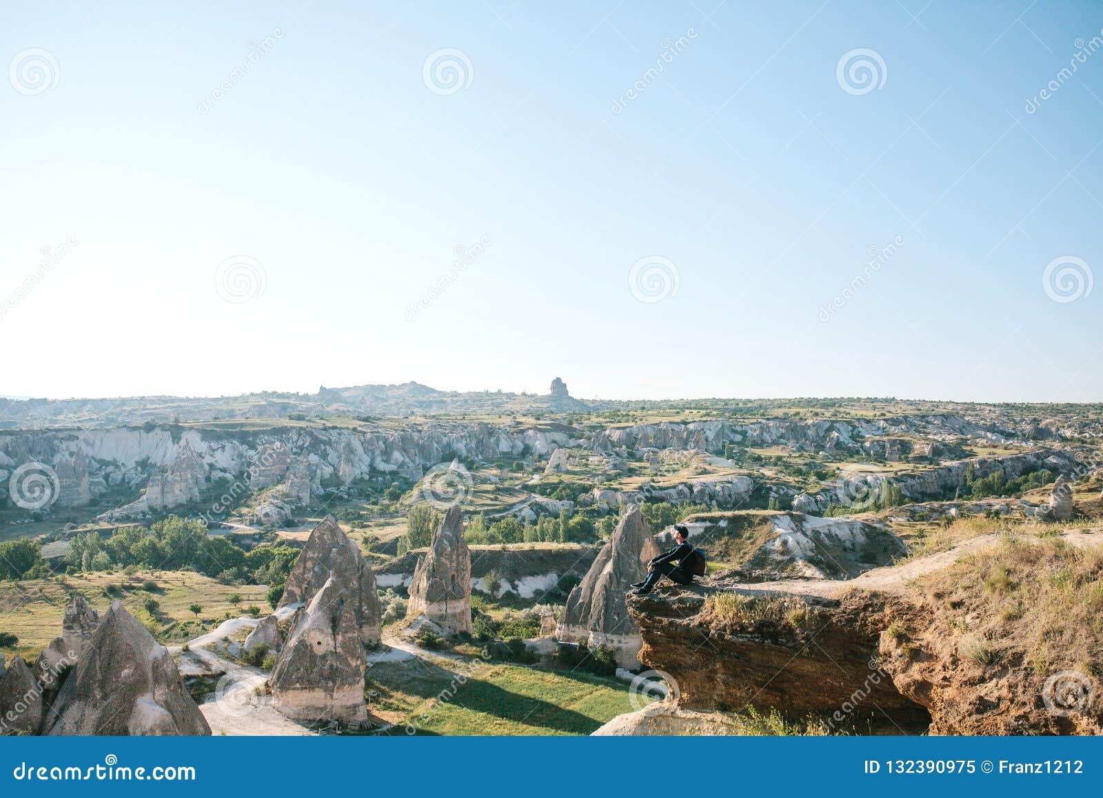 Een mens met een rugzak zit bovenop een heuvel in Cappadocia in Turkije