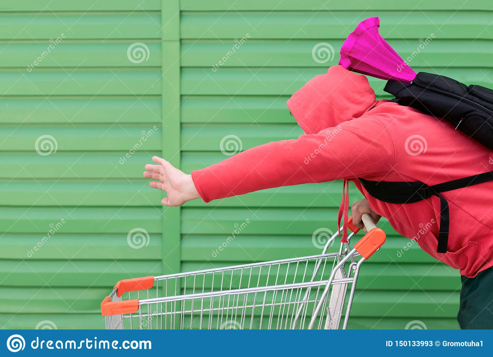 Een mens in een rood jasje met een kap op zijn hoofd en een rugzak op zijn rug met een gekleurd pakket rolt snel de kar van