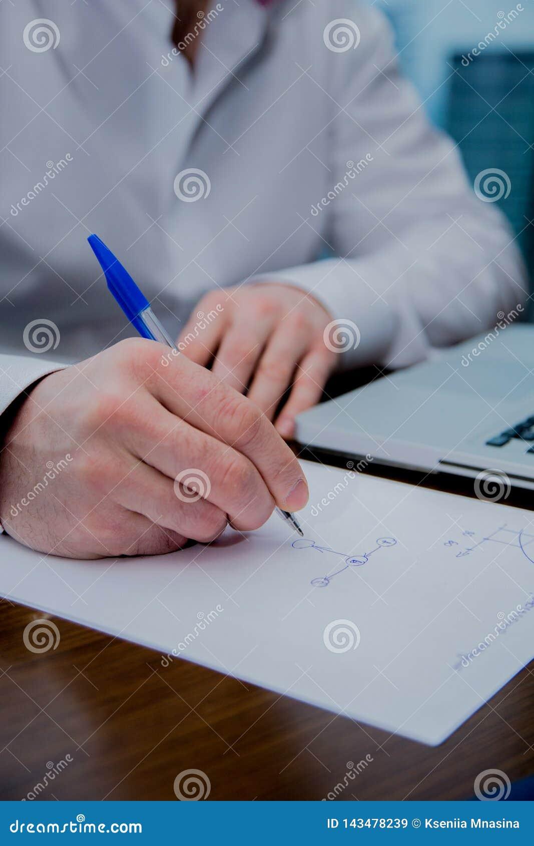 Een mens schrijft met een pen op een blad van document, zichtbare computer