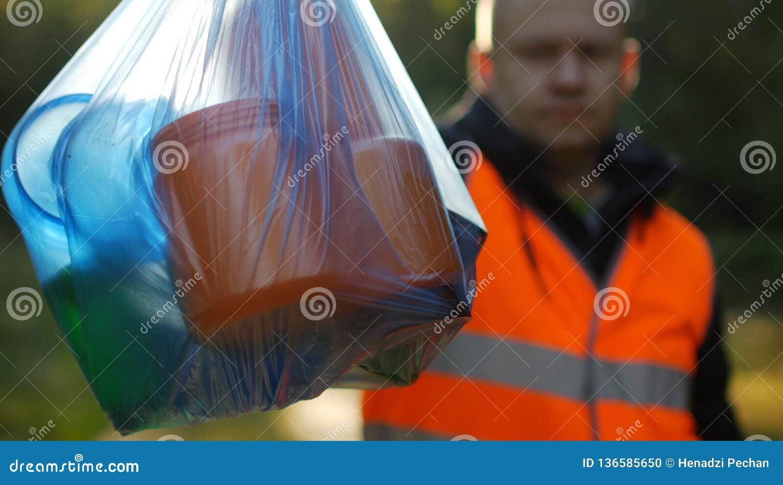 Een mens in een signaal oranje vest houdt een pakket met huisvuil op de achtergrond van aard, bos, close-up, garbagecollection