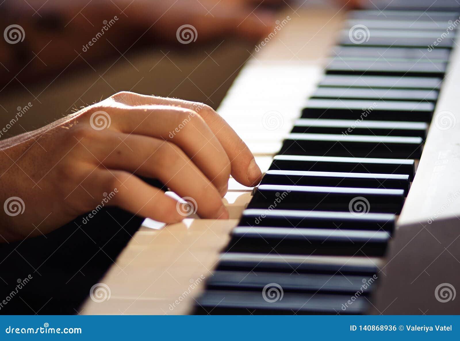 Een mens speelt een melodie op een toetsenbordinstrument