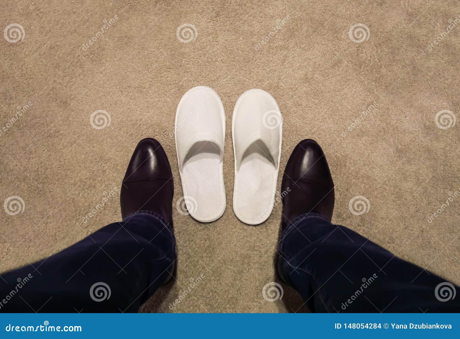 Een mens verandert zijn schoenen, opstijgt zijn schoenen, draagt hij witte pantoffels