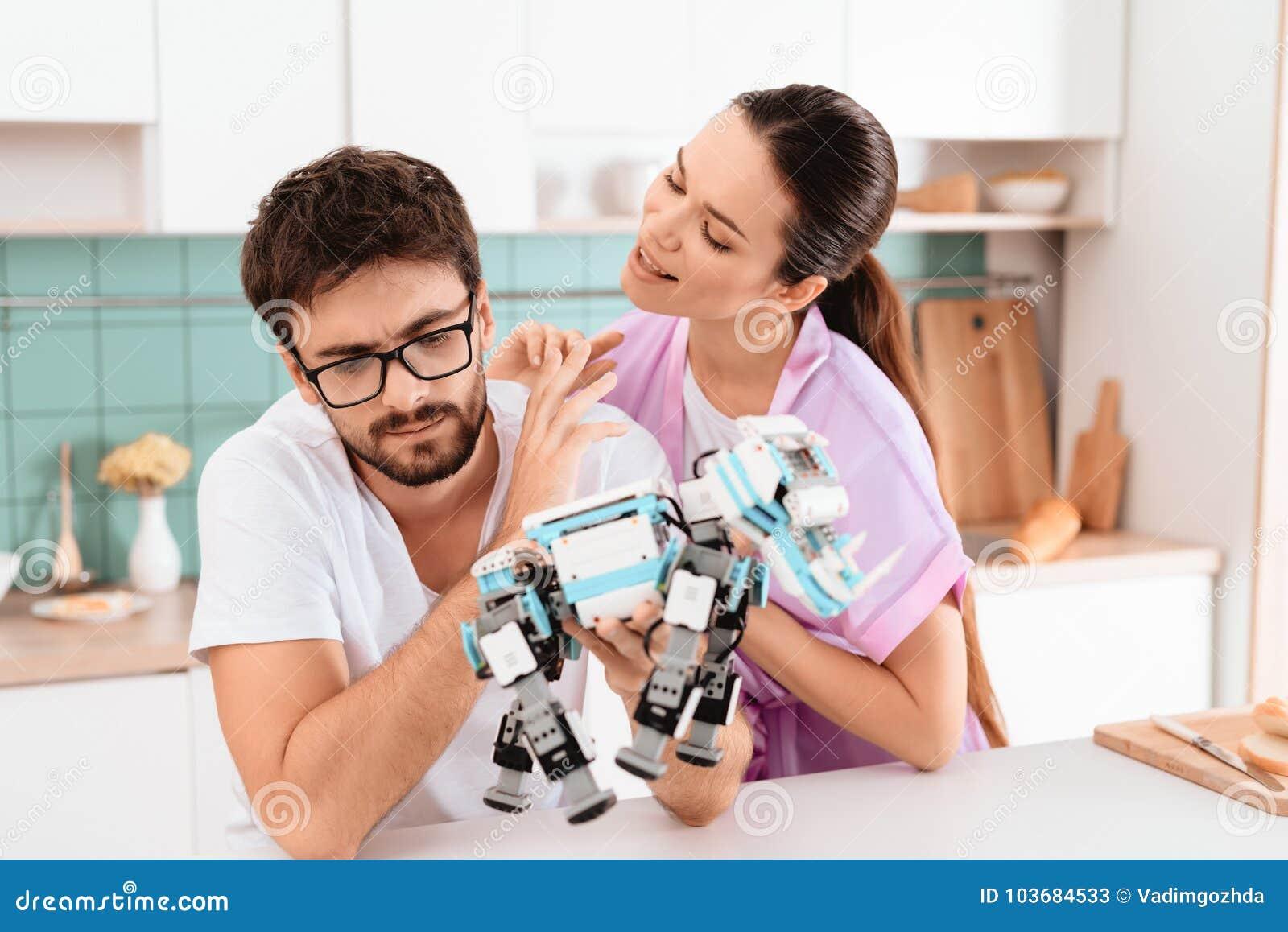 Een mens verzamelt een robot in de keuken De vrouw spreekt affectionately aan hem De man haalt weg het op
