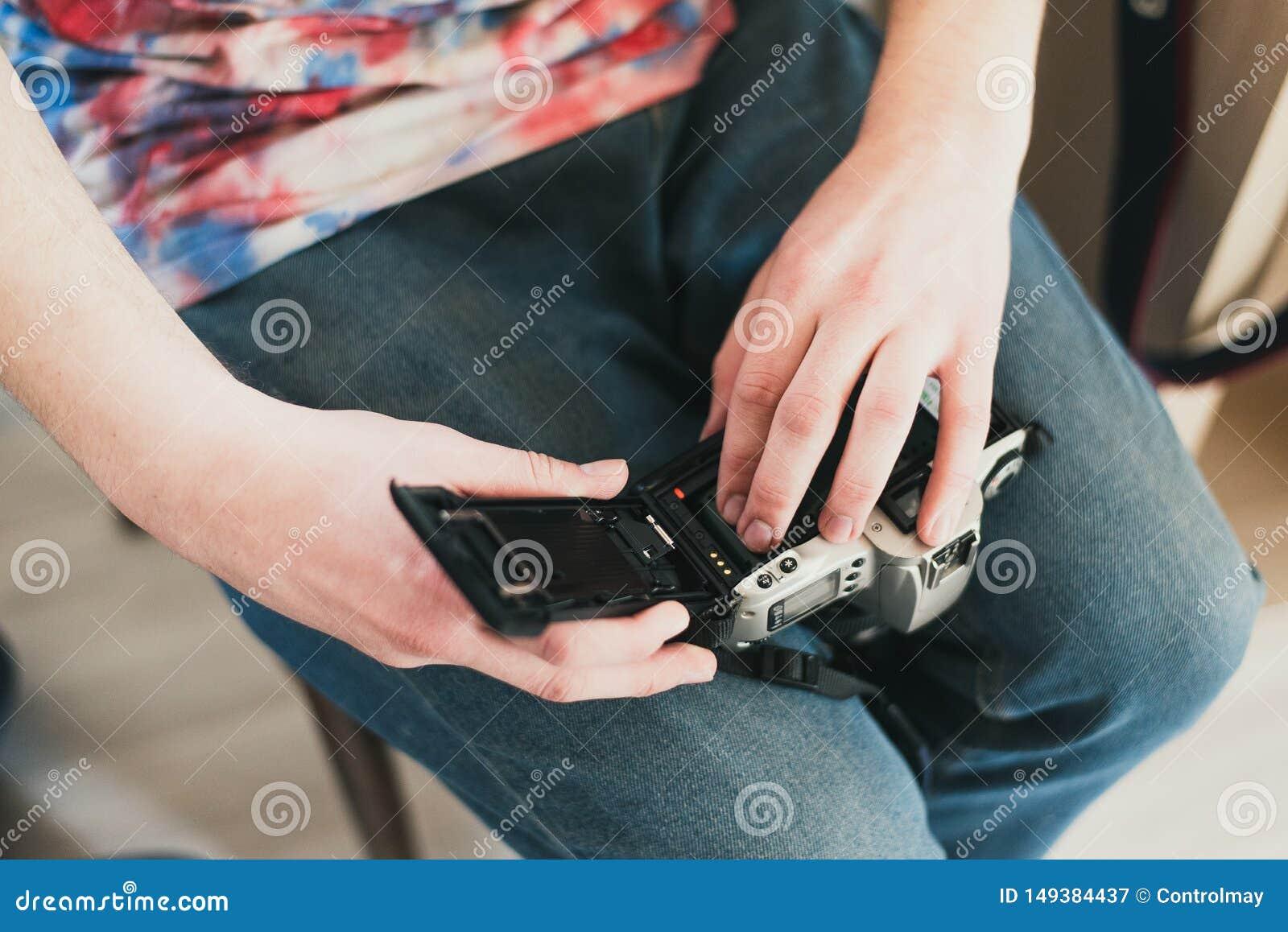 Een mens vult de camerafilm gezette film in de camera zet de band in de machine