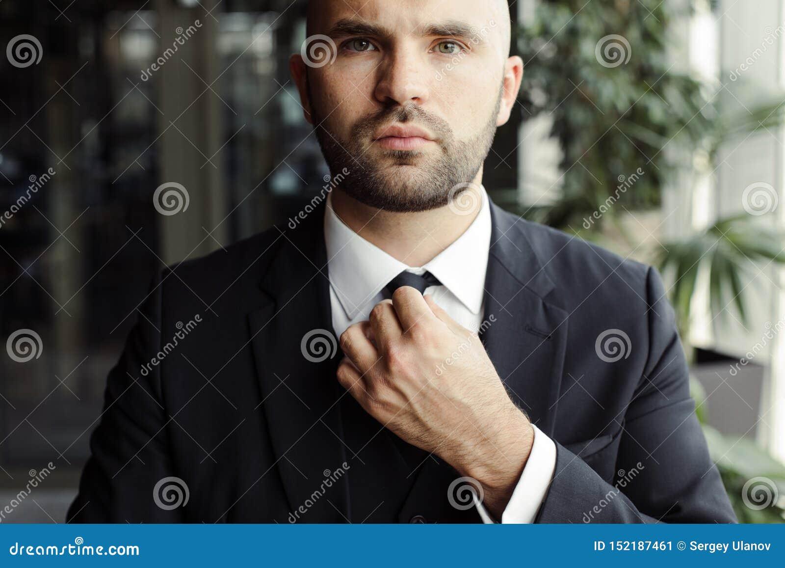 Een mens in een zwart kostuum maakt zijn band recht