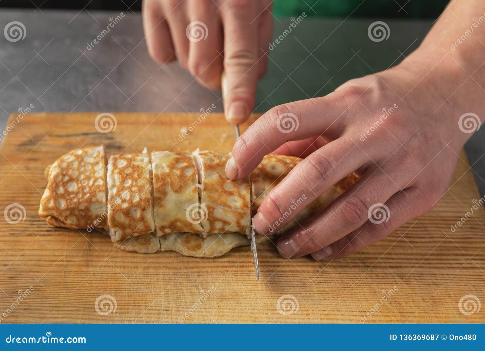Een mes in zijn hand snijdt een broodje van rijst close-up op een houten raad