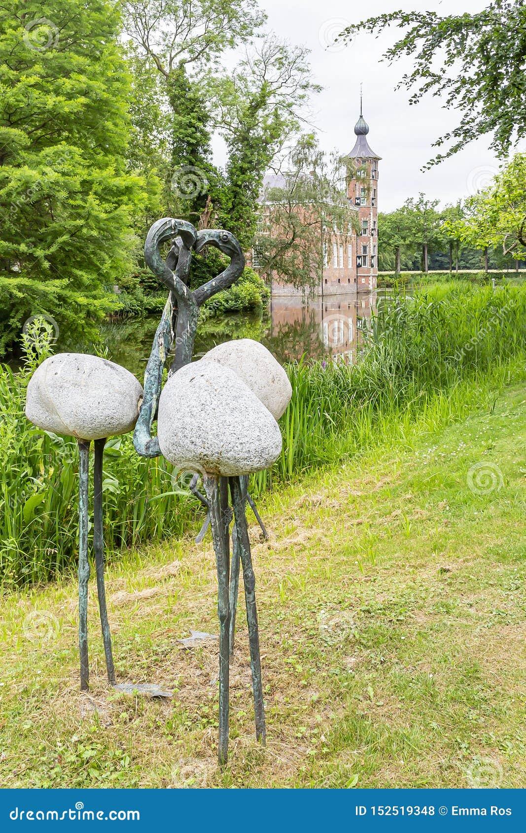Een modern standbeeld van drie flamingo s met op de achtergrond het mooie Kasteel Bouvigne dichtbij Breda, Nederland