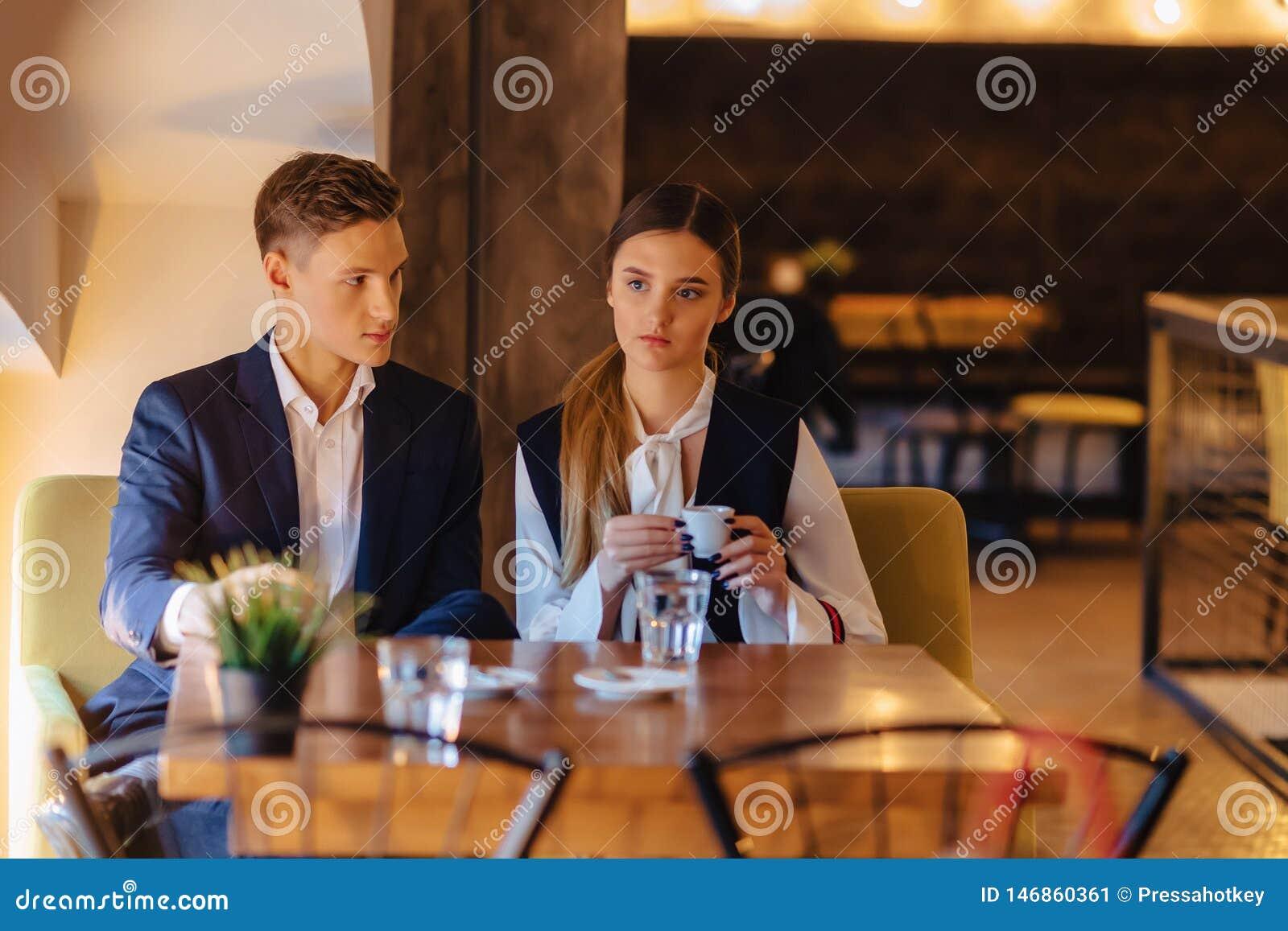 Een modieus paar drinkt ochtendkoffie bij de koffie, de jonge zakenlieden en freelancers