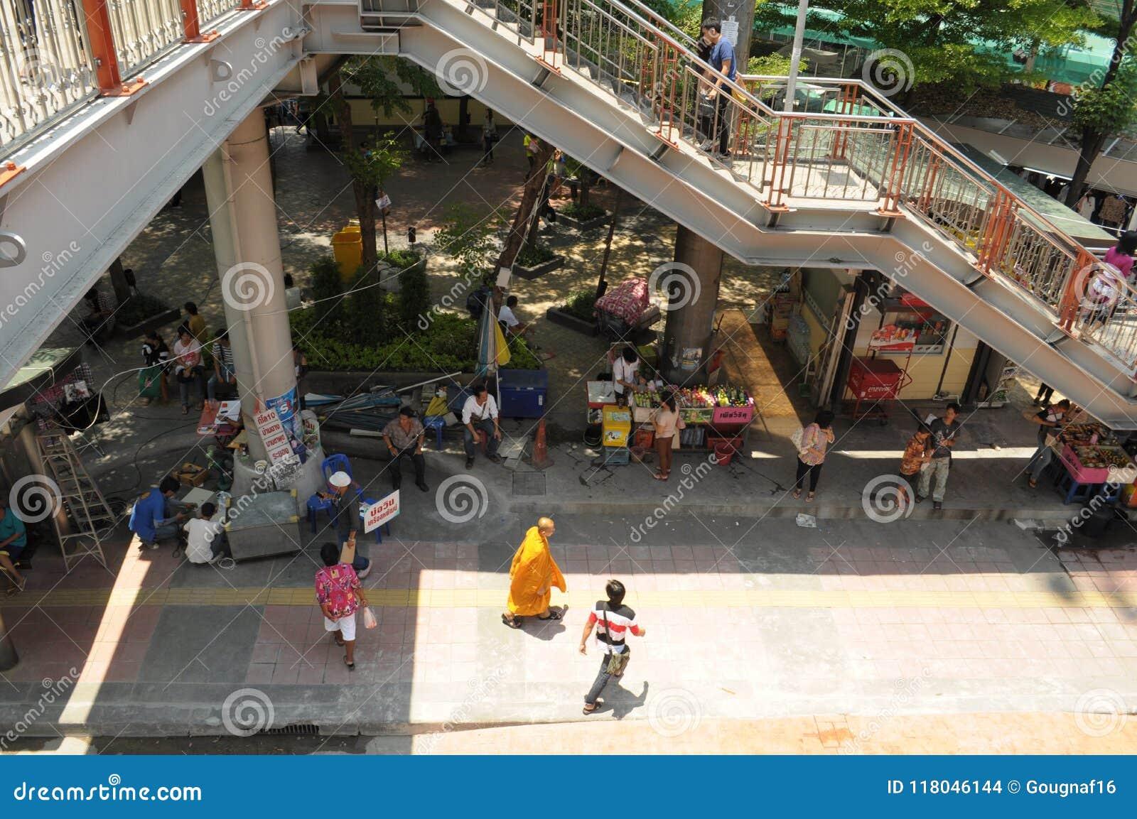 Een monnik onder andere voetgangers gaat door de boxen in Victory Monument in Bangkok, Thailand over