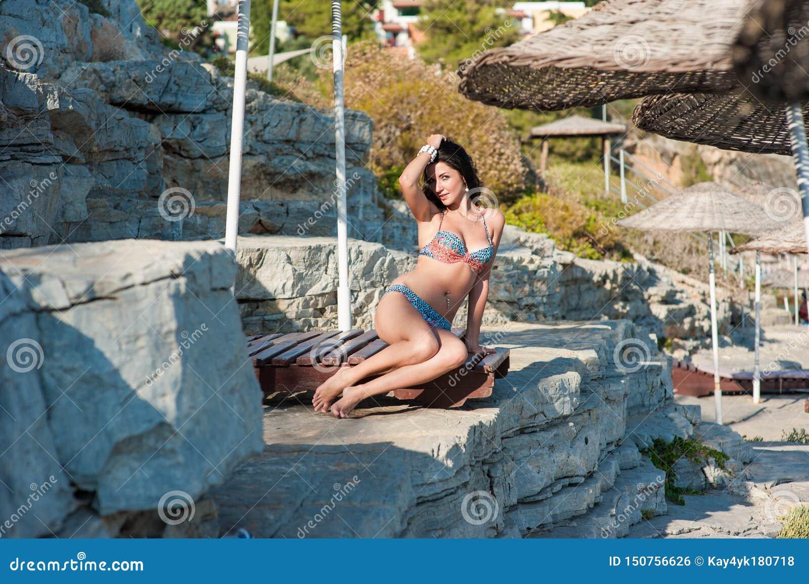 Een mooi brunette zit op een lanterfanter jong meisje in sexy bikini