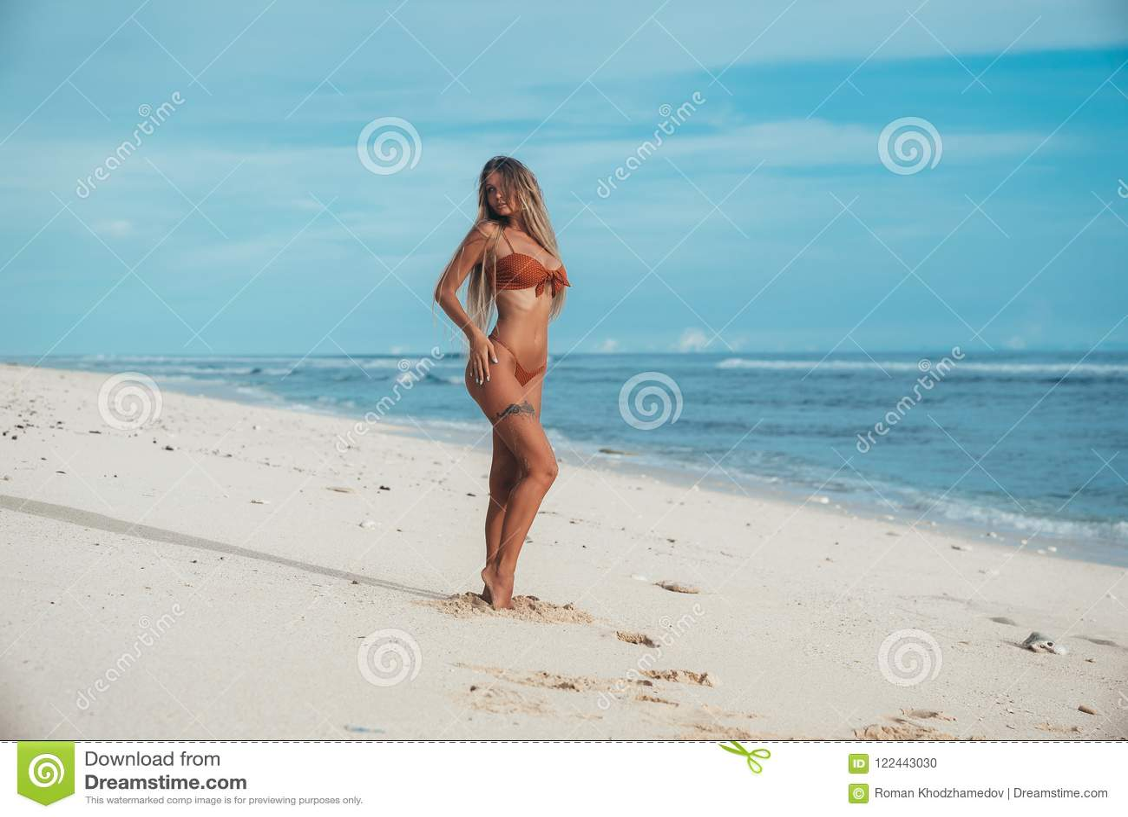 Een mooi jong blonde staat te zwemmen op het punt, draaide zij van het overzees aan het zand om ervoor te zorgen dat zij niet ver