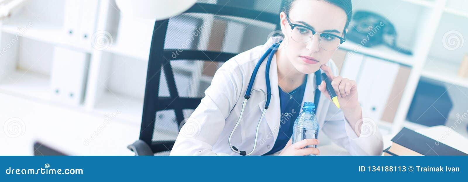 Een mooi jong meisje in een witte robe zit bij het computer bureau, het houden van een open fles water en het lopen