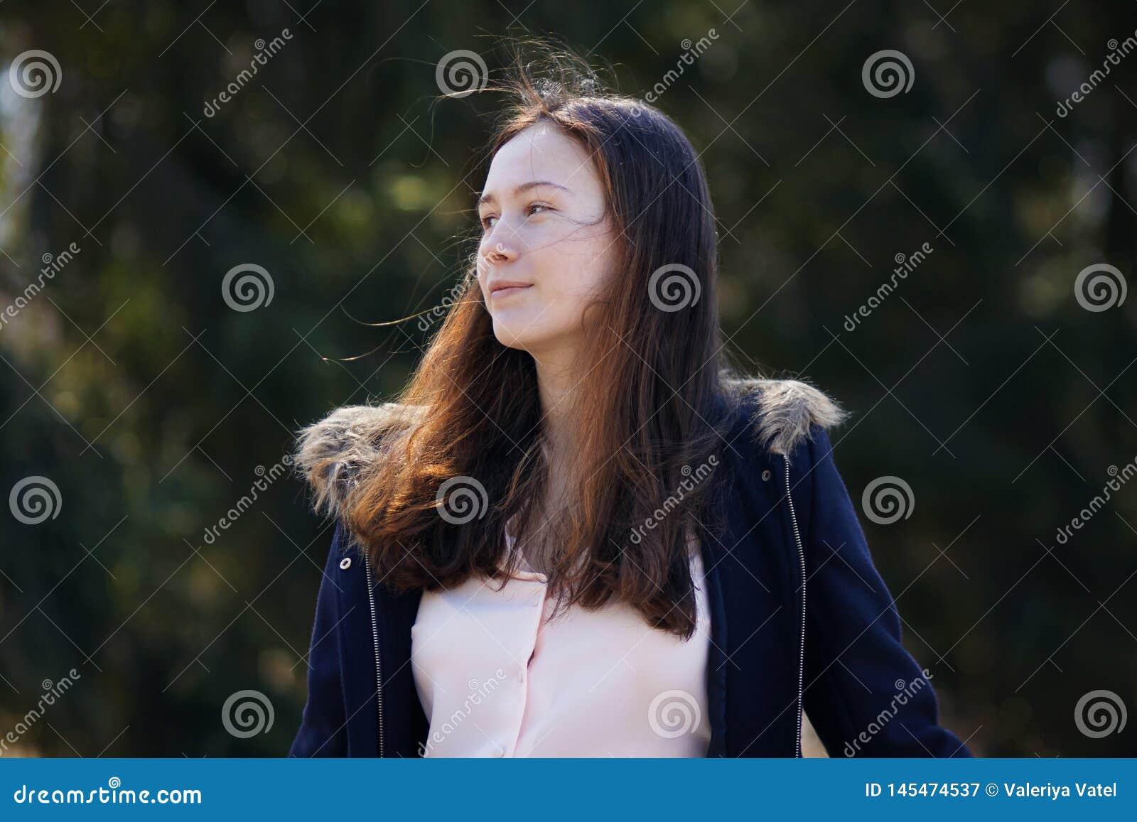 Een mooi meisje in een blauwe laag met los roodachtig haar