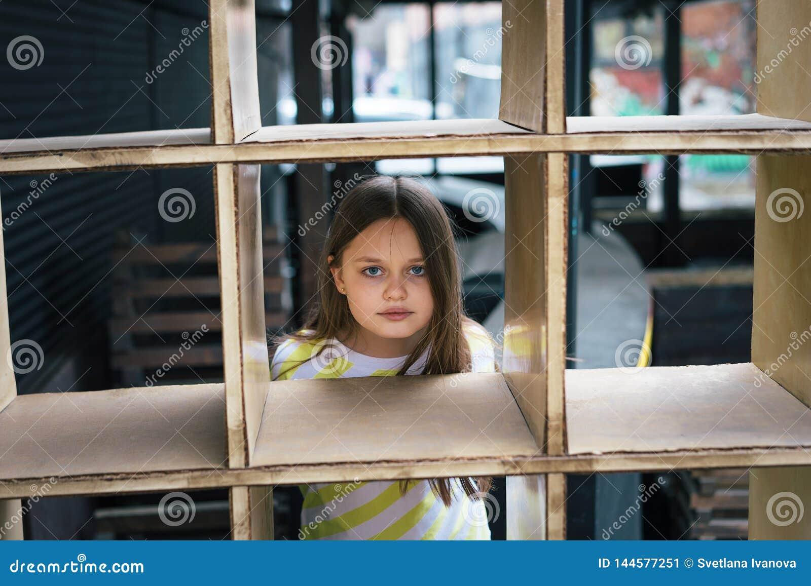 Een mooi meisje die uit van achter een kooi-vormige structuur kijken Spelconcept