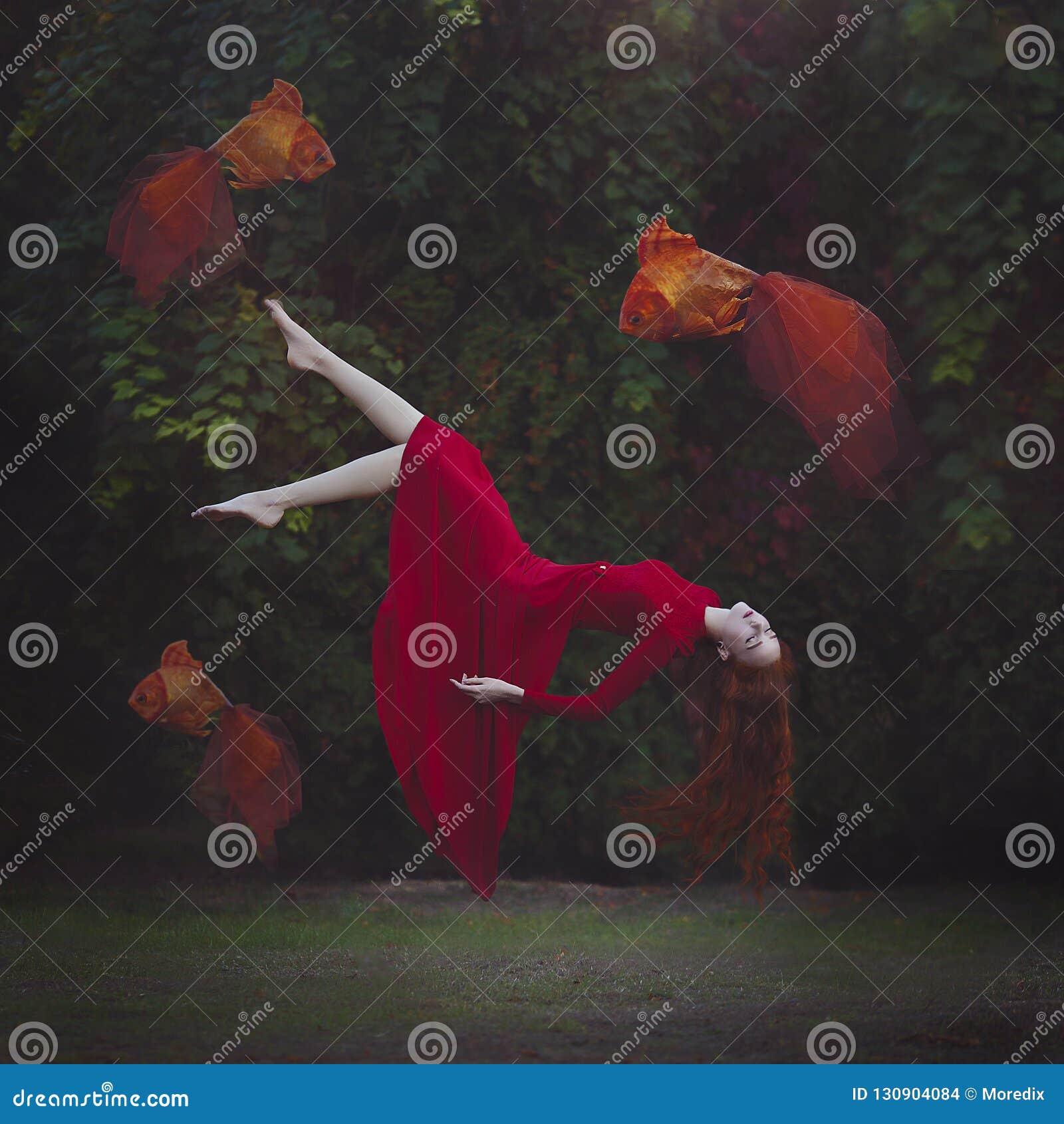 Een mooi meisje met lang rood haar in een rode kleding levitatie ondergaat boven de grond Surreal magische foto van een vrouw met