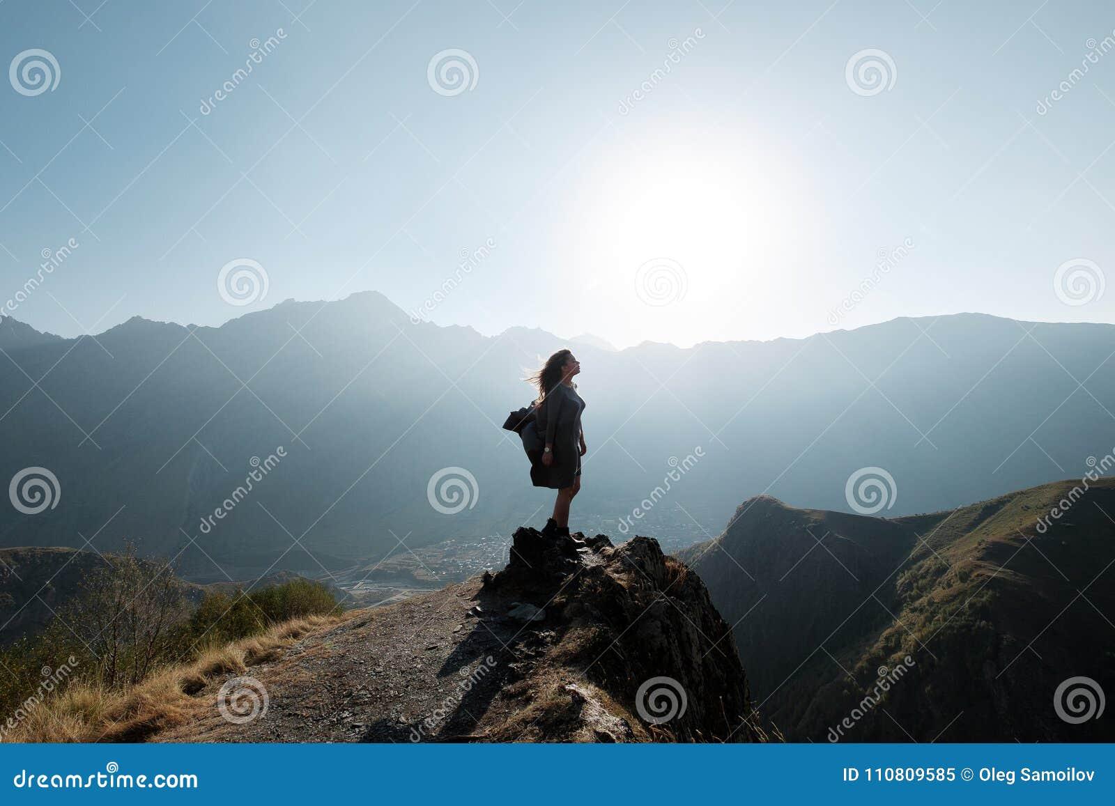 Een mooi meisje in een vliegende kleding zit op een klip overziend de bergen