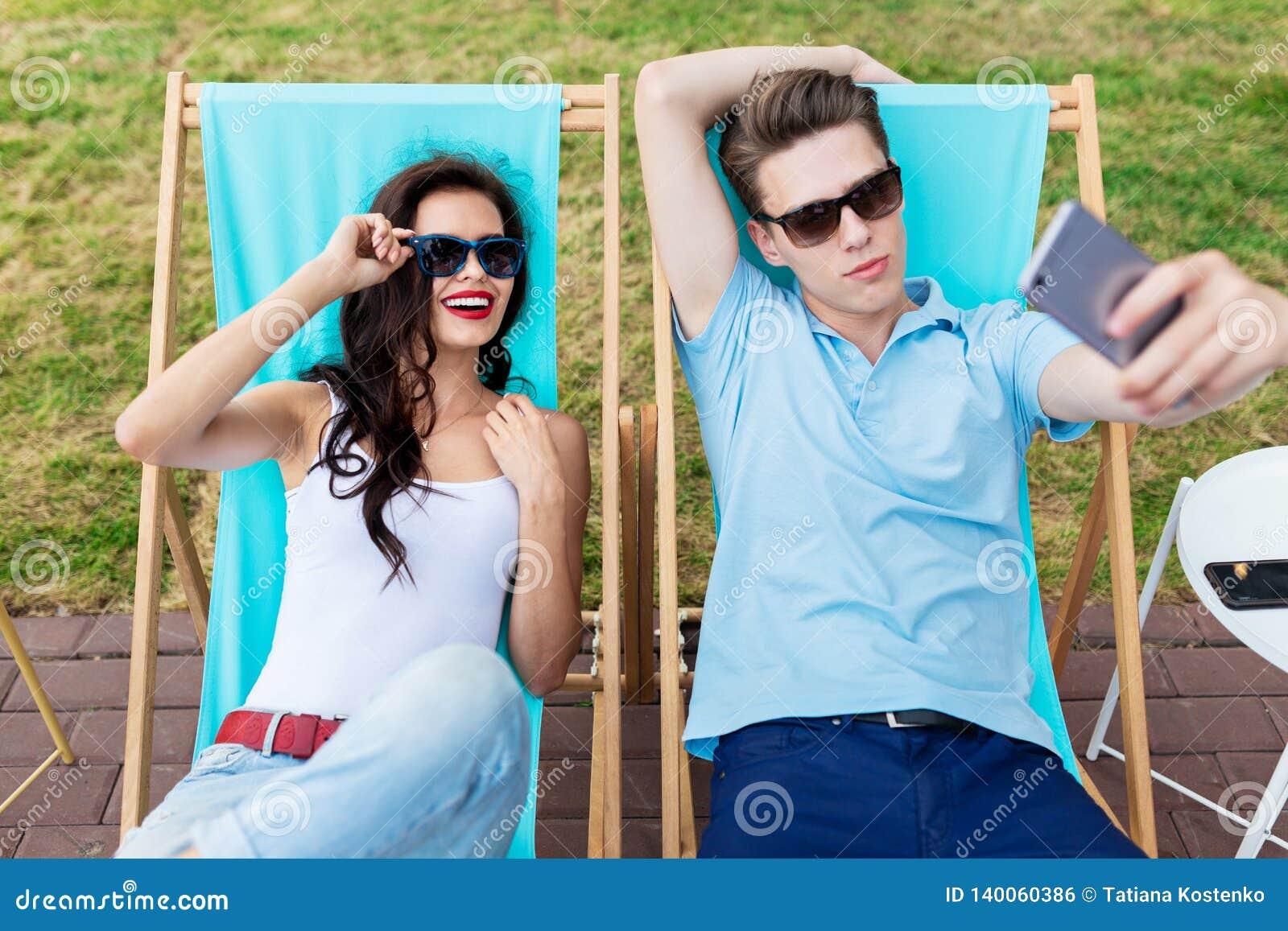 Een mooi paar in de zonnebril ligt op de ligstoelen op het gazon in de aardige de zomerkoffie vermaak