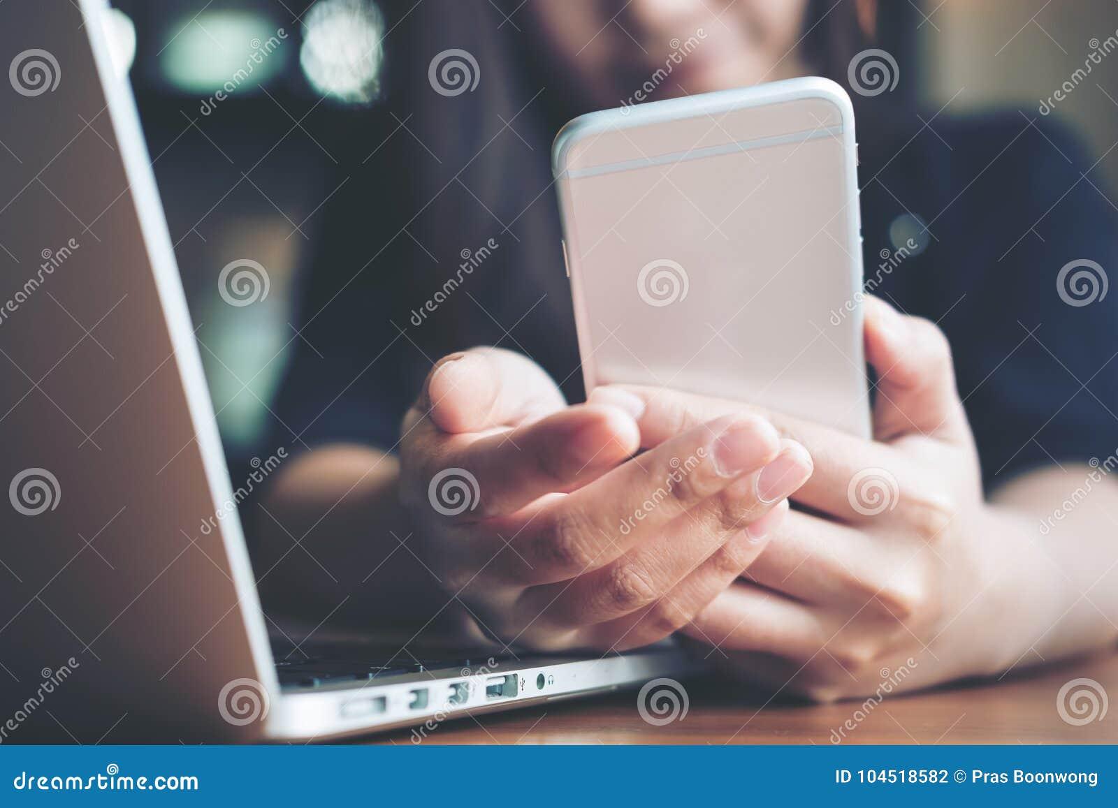 Een mooie Aziatische vrouw met smileygezicht holding en het bekijken slimme telefoon terwijl het gebruiken van laptop op houten l