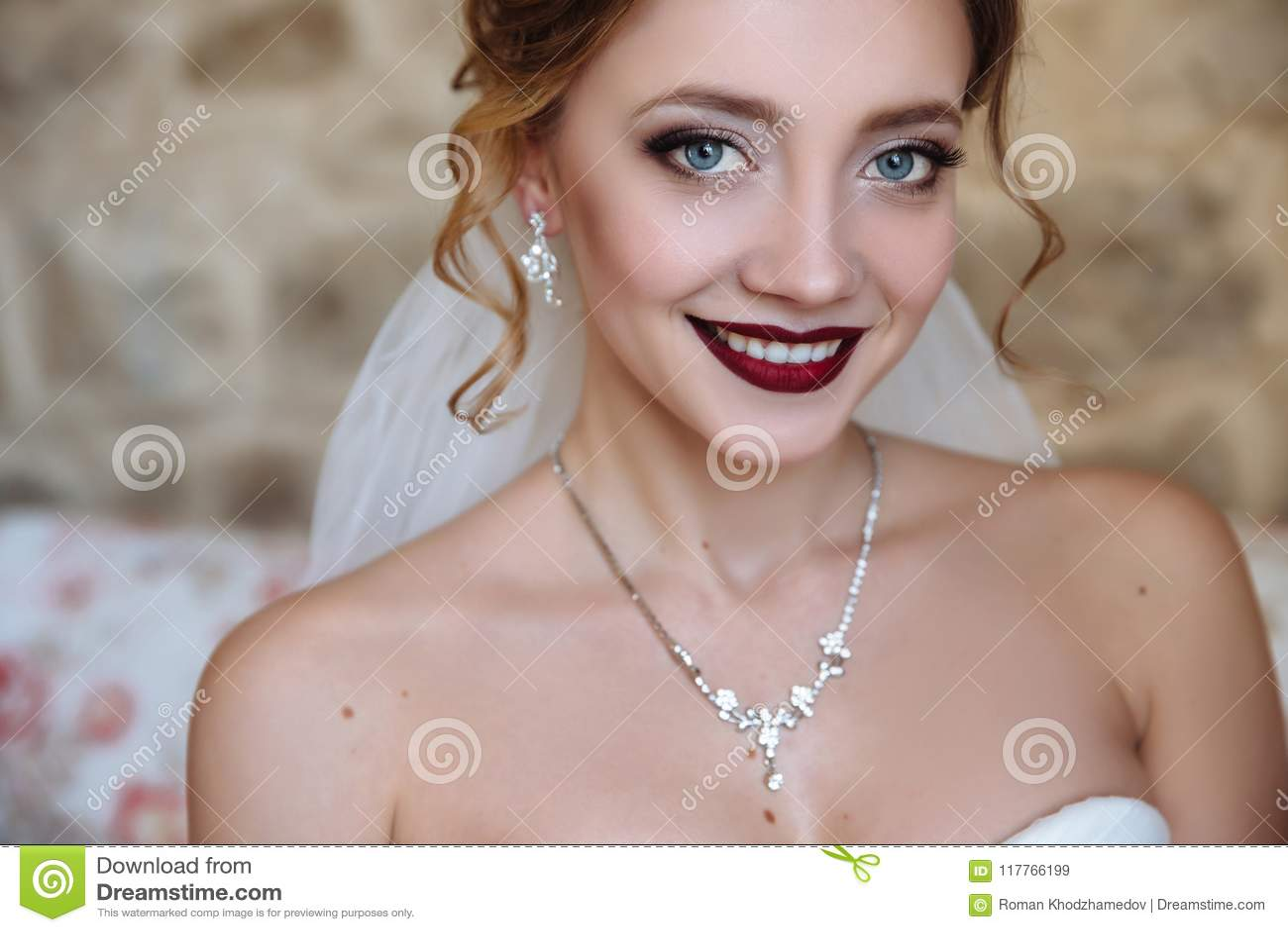 Een mooie bruid en een kleding met open schouders Een close-up van een meisje met een gevoelige oogmake-up en rode lippen wordt g