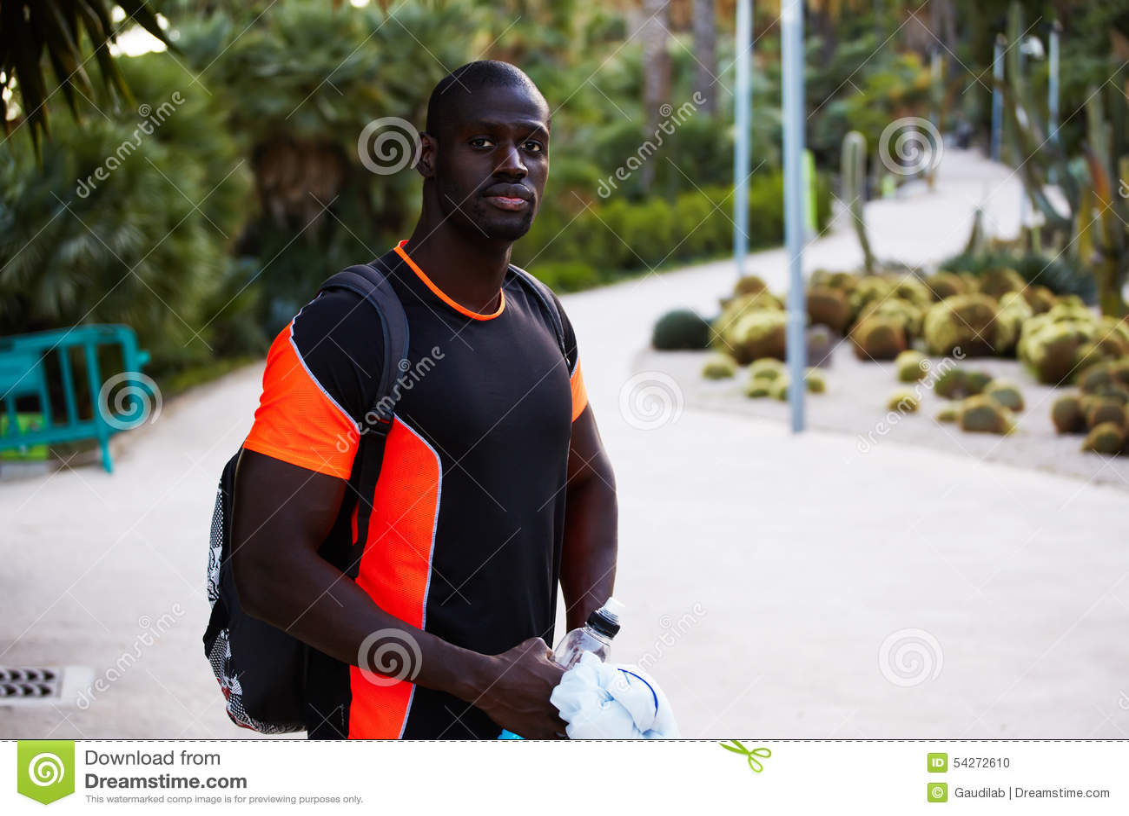 Een mooie donker-gevilde atleet gaat want in het park met een rugzak aanstoot