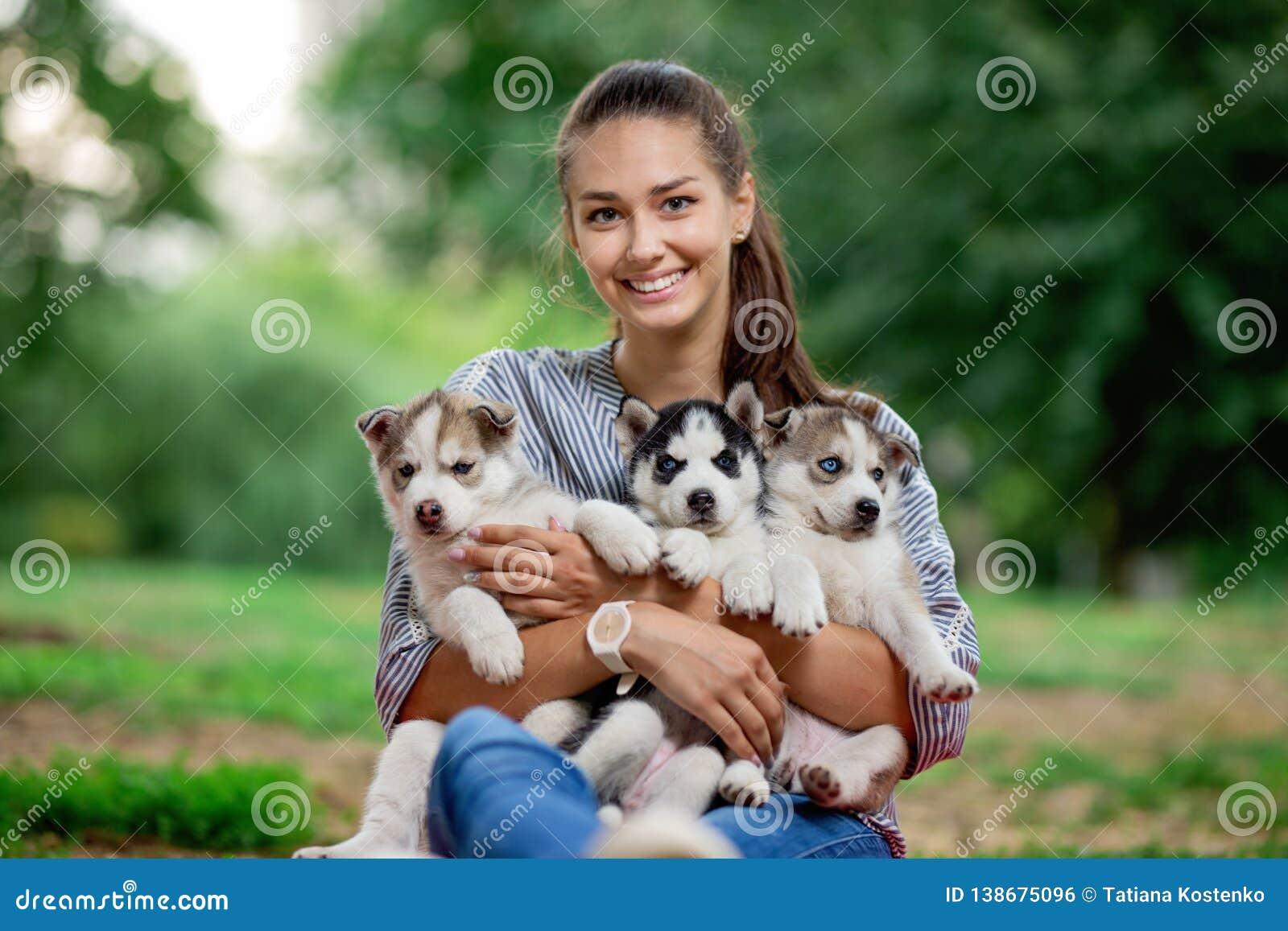 Een mooie glimlachende vrouw met een paardestaart en het dragen van een gestreept overhemd houdt drie zoete schor puppy op het ga