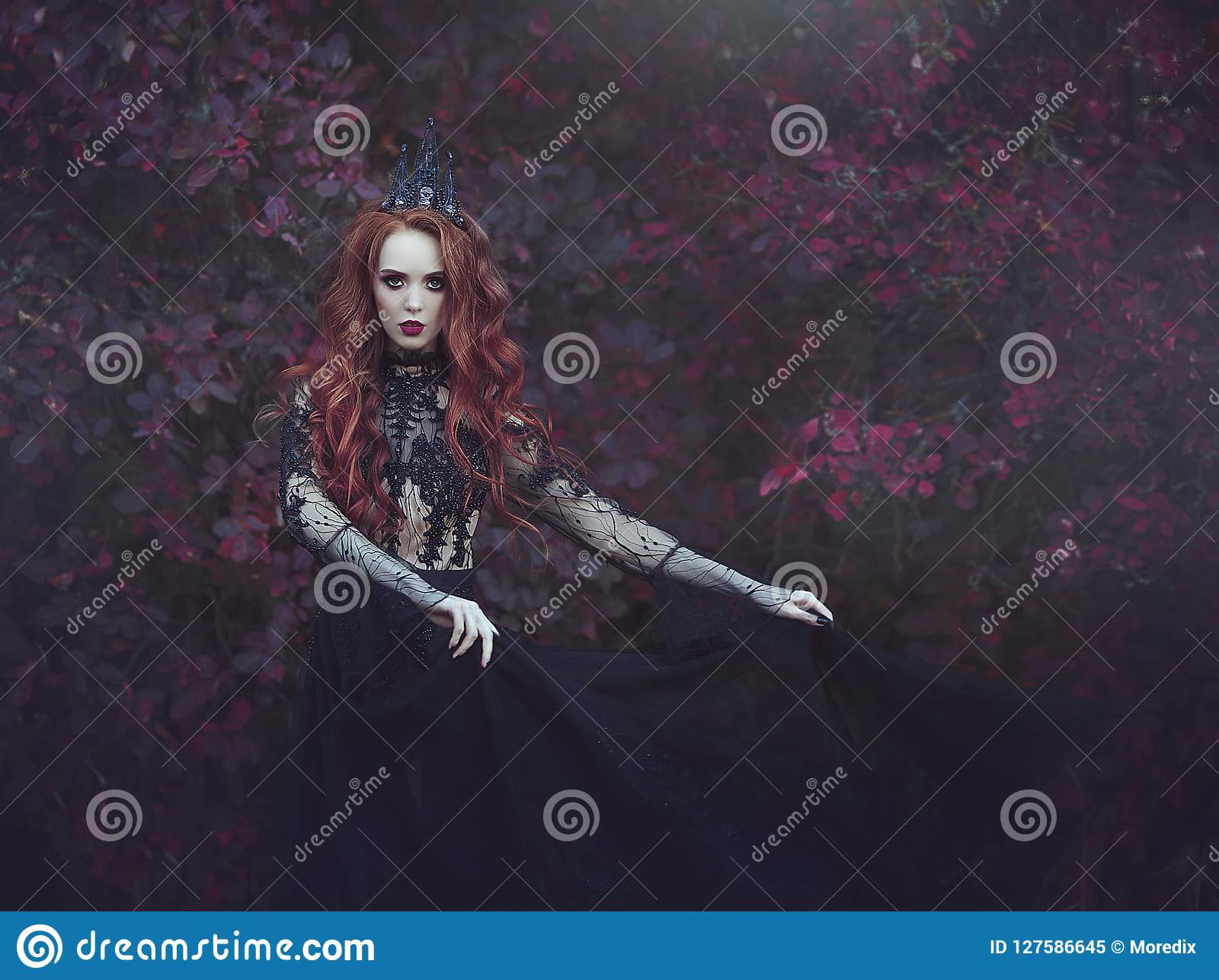 Een mooie gotische prinses met bleke huid en het lange rode haar die een kroon en een zwarte dragen kleden zich tegen de achtergr