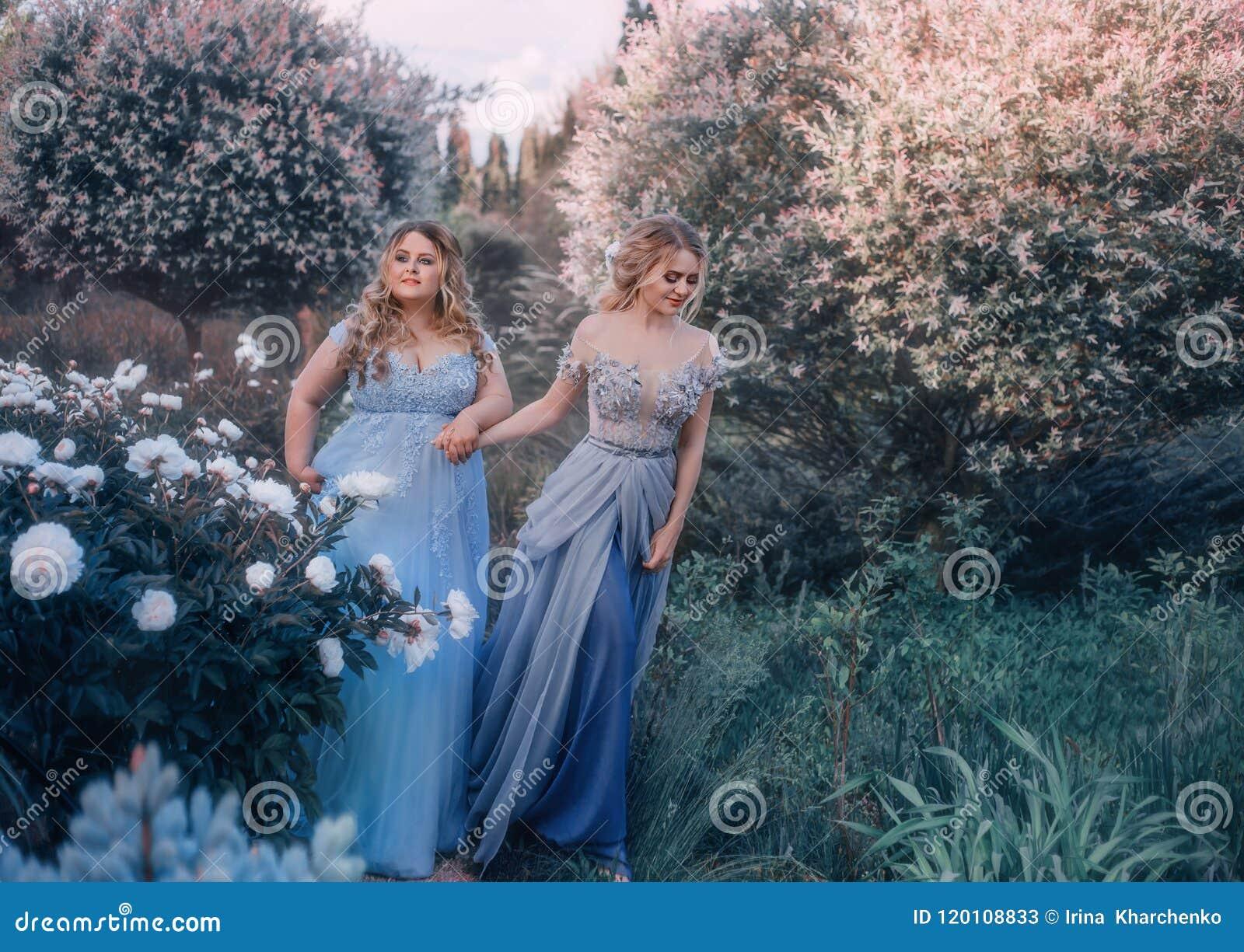 Een mooie grote vrouw houdt een breekbaar blondemeisje in haar hand Twee prinsessen in luxueuze blauwe kleding tegen