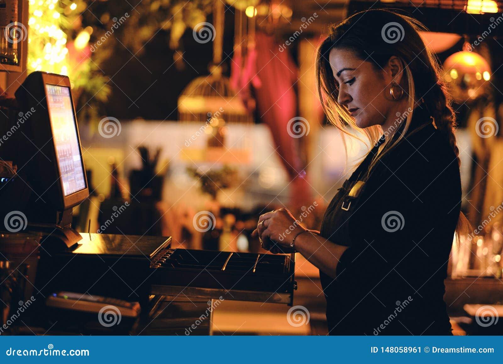Een mooie jonge vrouw bij het bureau in een restaurant