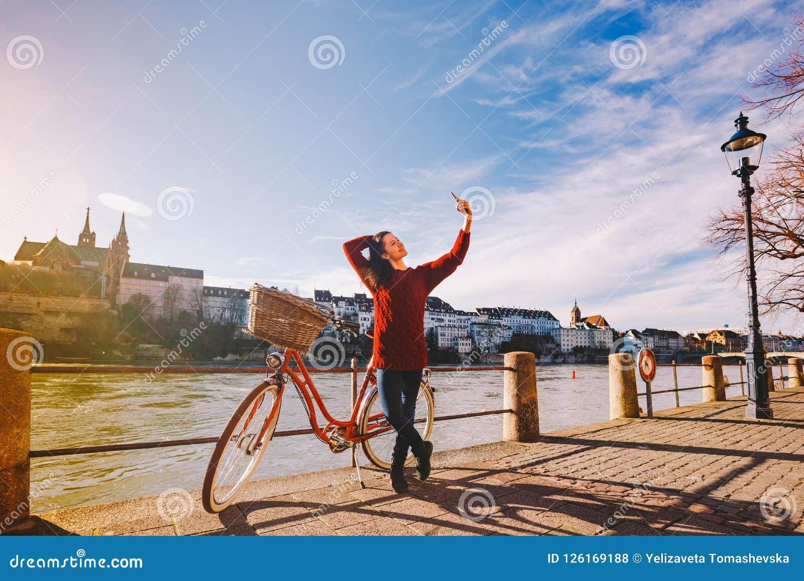 Een mooie jonge vrouw met een retro rode fiets maakt een foto van zich in de oude stad van Europa op de Rivier Rijn embankm