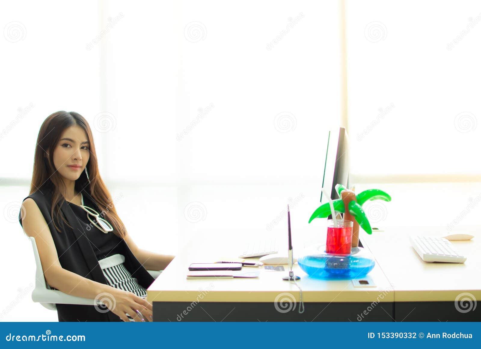 Een mooie vrouwenzitting in het bureau en planning voor reis