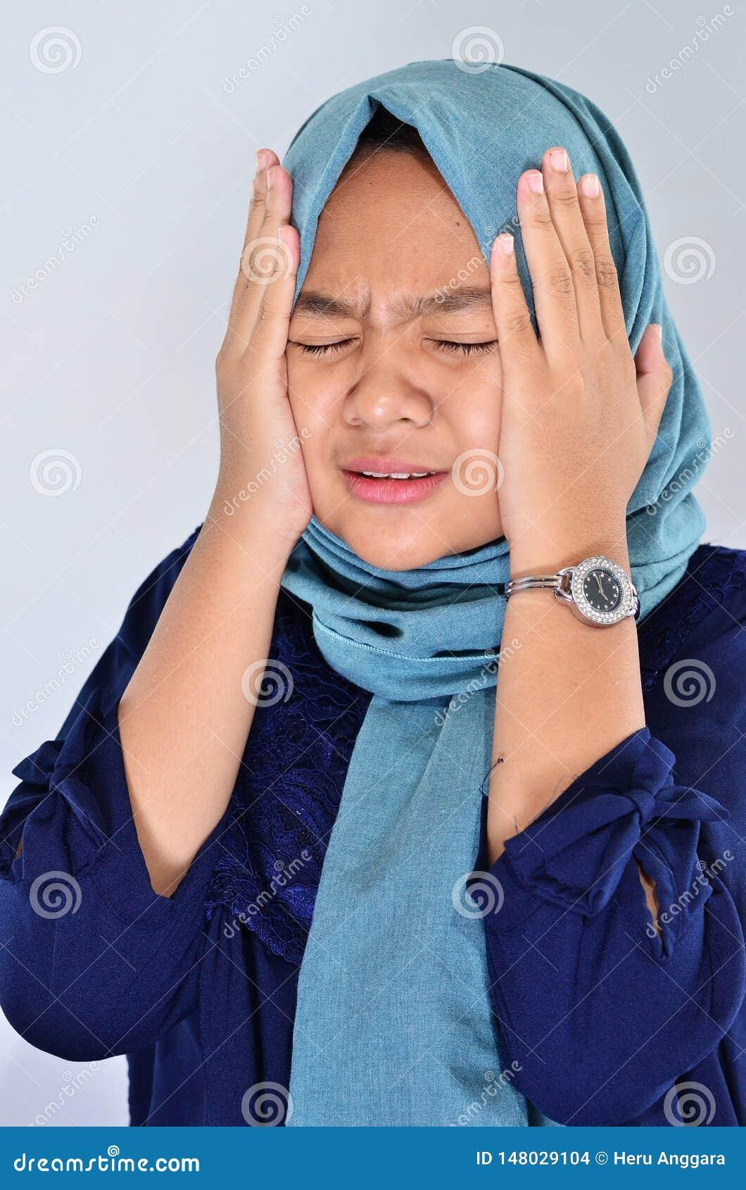 Een Moslimvrouw in een hijab schreeuwt met het houden van haar gezicht gebruikend haar handen Het Aziatische meisje is gedeprimee