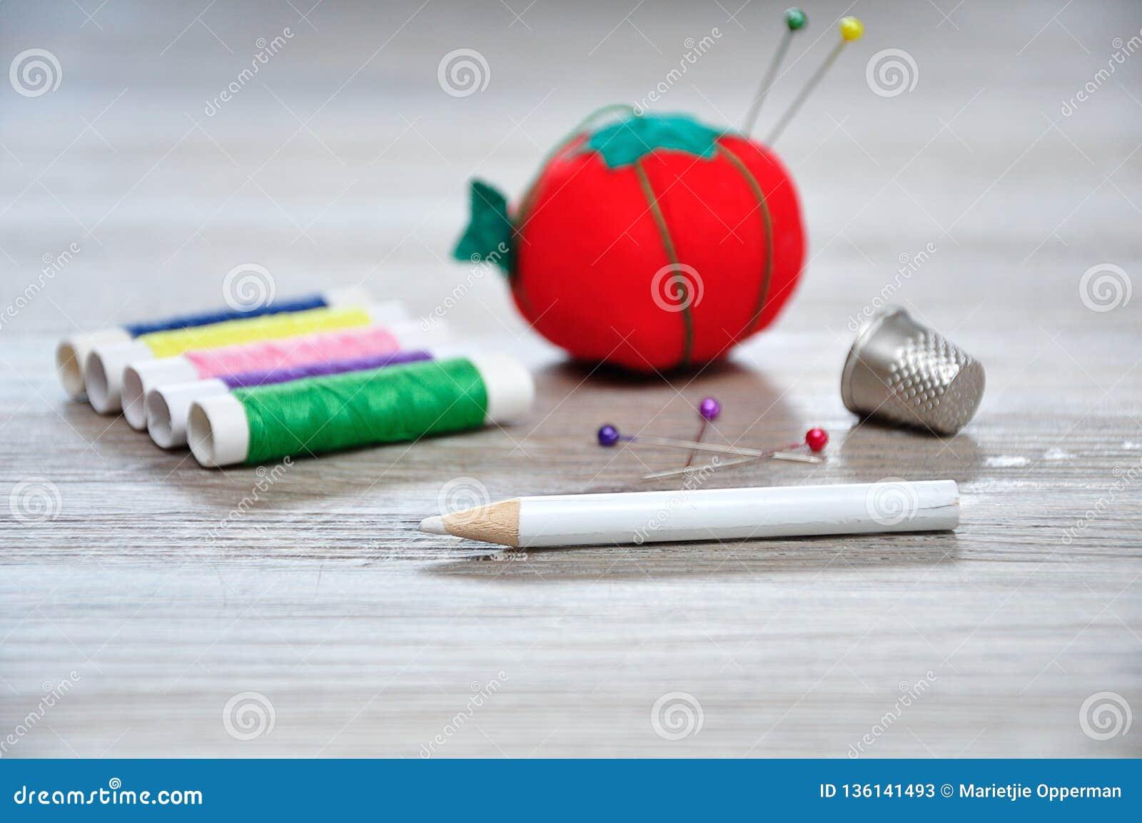 Een naaisterpotlood met uit het kussen van de nadrukspeld als rode tomaat, broodjes wordt gevormd van draad en een vingerhoedje d