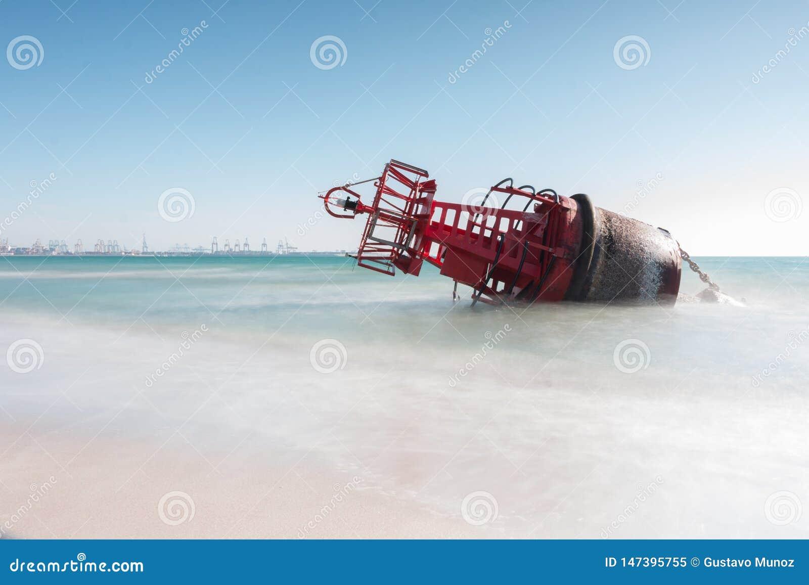 Een navigatieboei liep op het strand vast door de sterke stromen van een onweer met een lange expositie voor een zijdeeffect