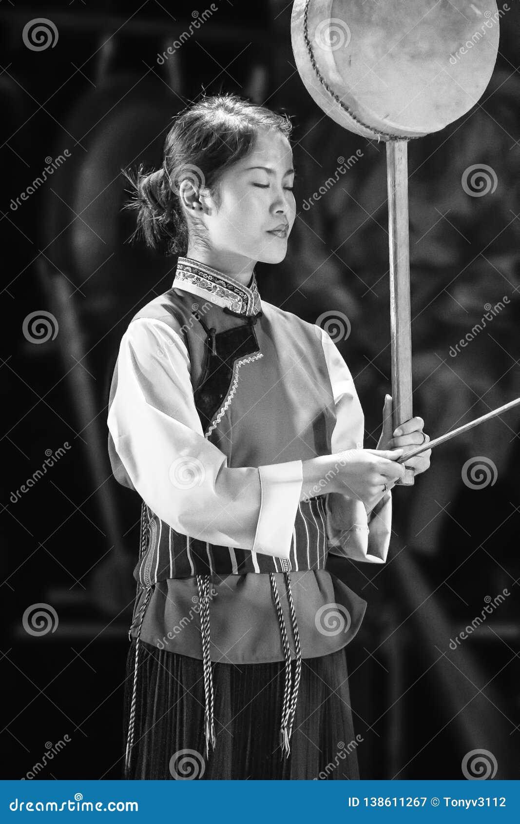 Een Naxi-vrouw presteert in een theater, Lijiang, China