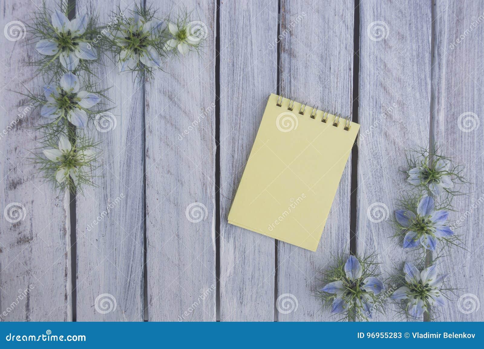 Een nota over een houten oppervlakte die door bloemen 5 wordt ontworpen