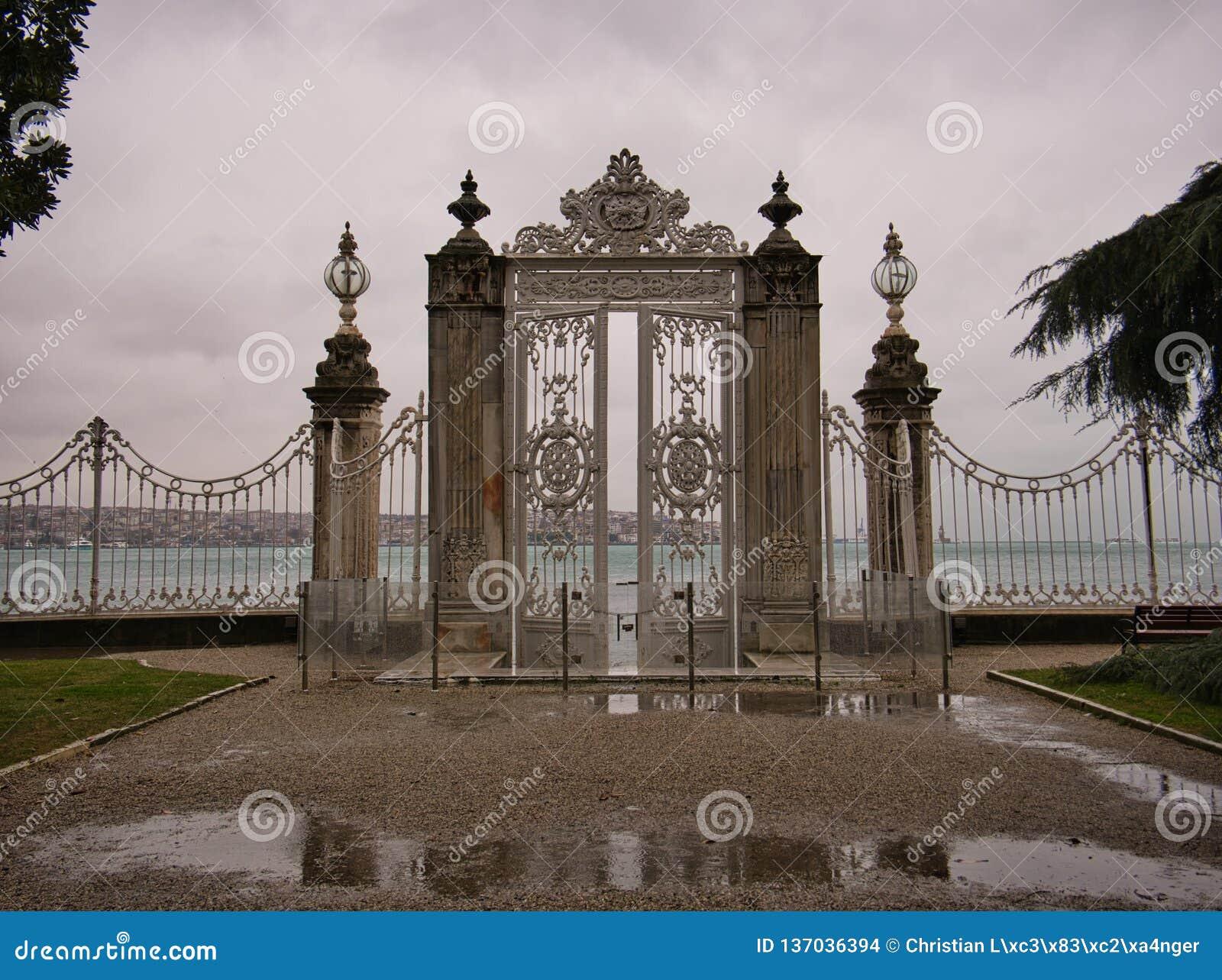 Een omheining met hoge kolommen en de poort in het paleis tuinieren