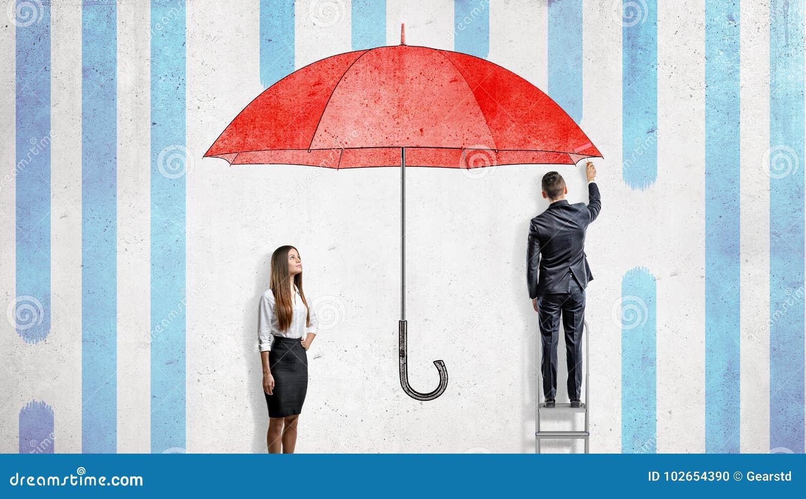 Een onderneemster bevindt zich dichtbij een muur waar een zakenman een reuze rode paraplu trekt die hen behandelen van de regen