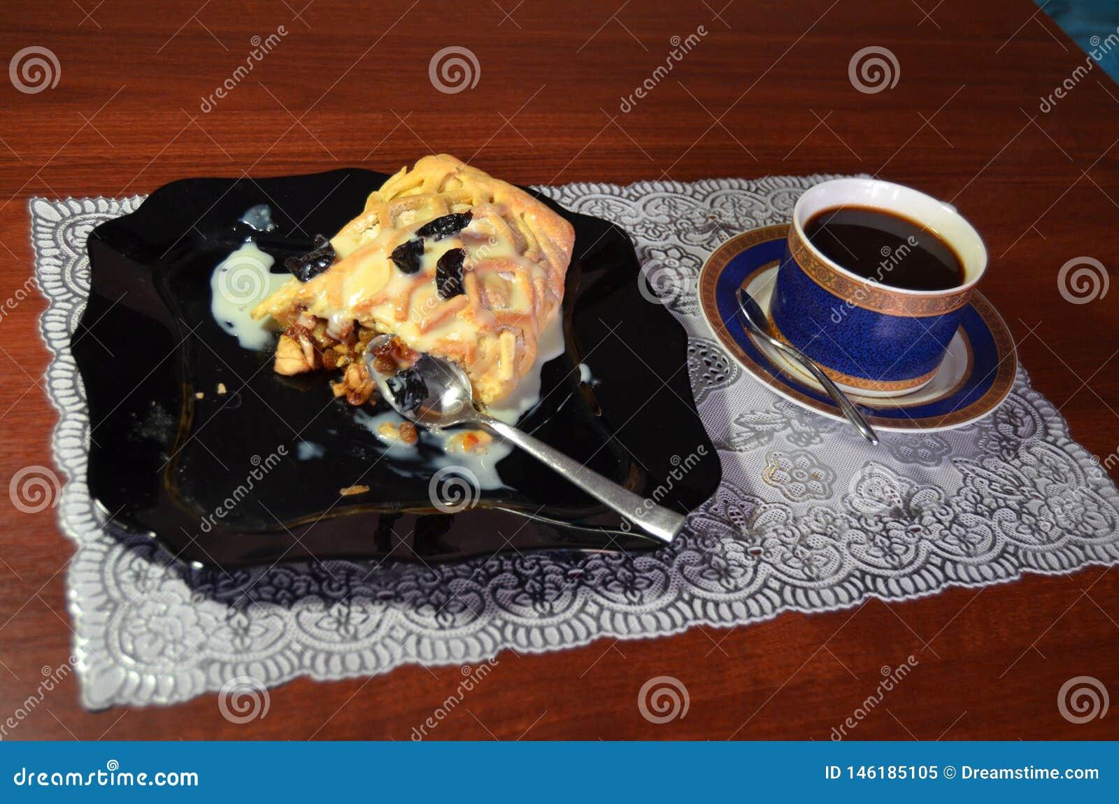 Een ontbijt van de strudel met appel en rozijn en zwarte koffie