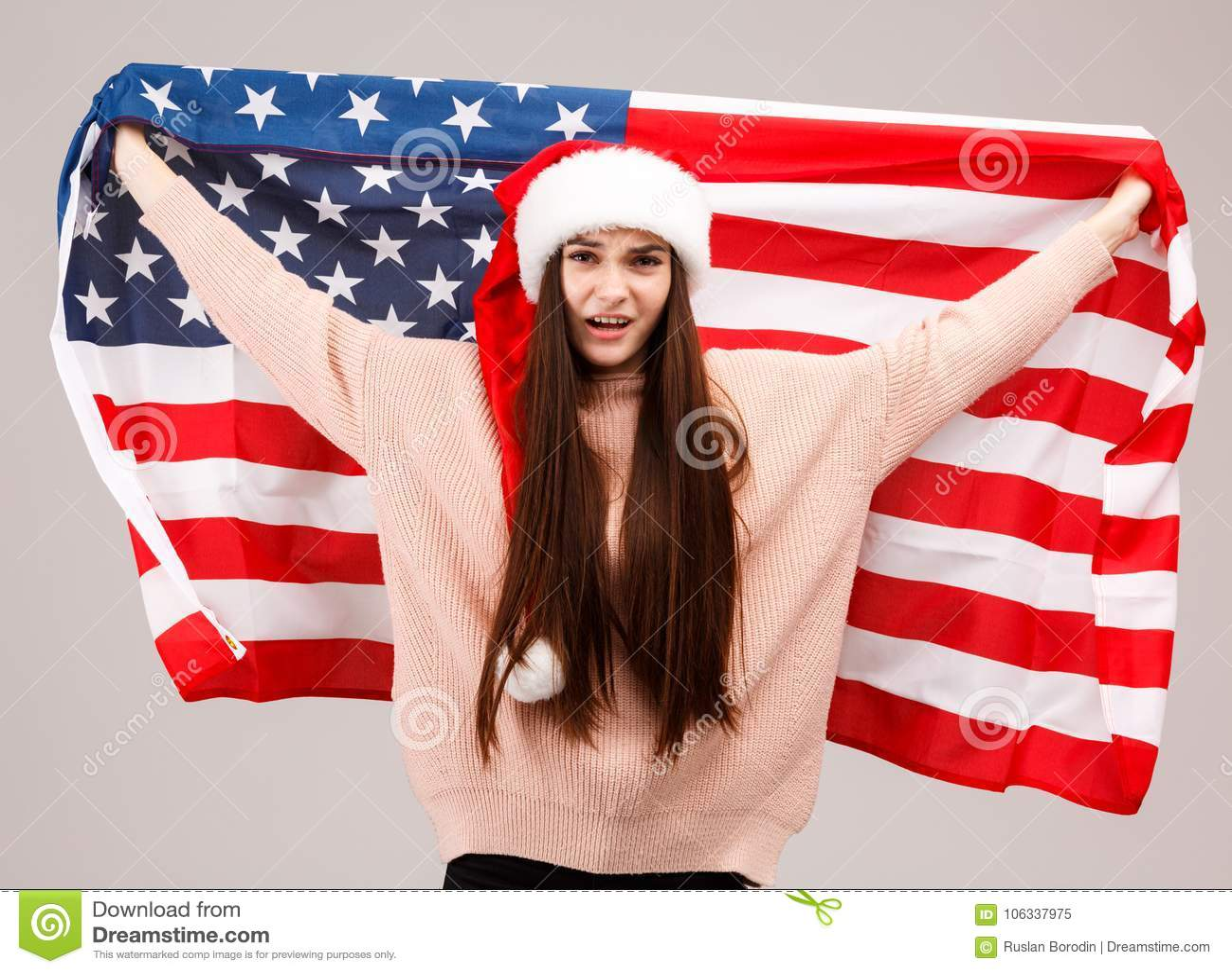 Een ontevreden meisje in een warme sweater en heeft Kerstmis GLB die een Amerikaanse vlag houden