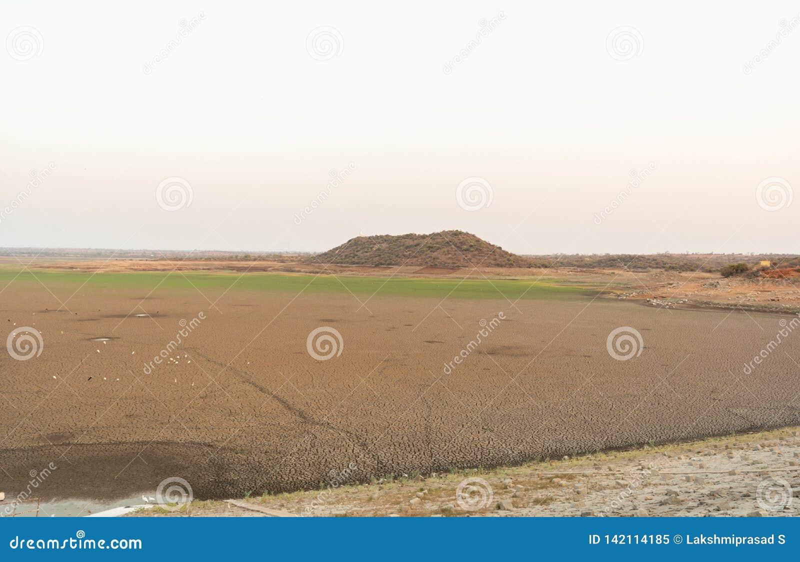 Een opgedroogde lege reservoir of een dam tijdens een de zomerhittegolf, een lage regenval en een droogte in het noordenkarnataka