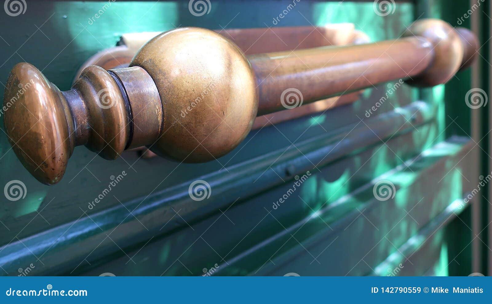 Een oud messingshandvat op de groene houten deur