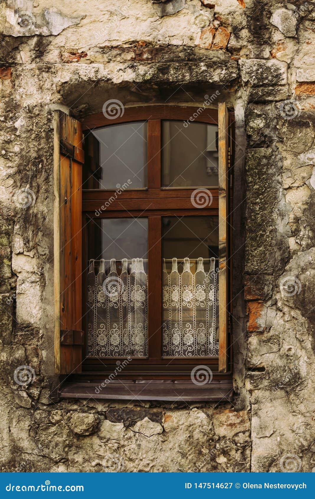 Een oud venster met open blinden in een oud huis