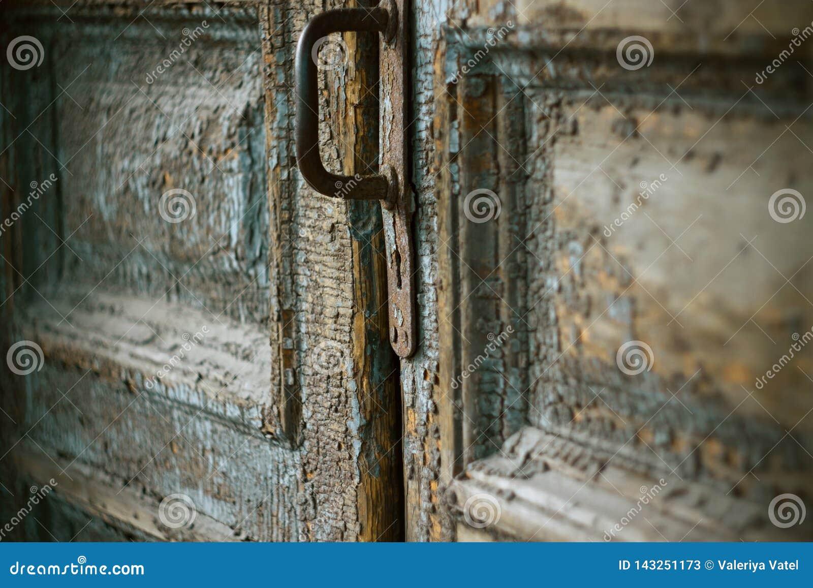Een oude deur met een roestig handvat en een sleutelgat
