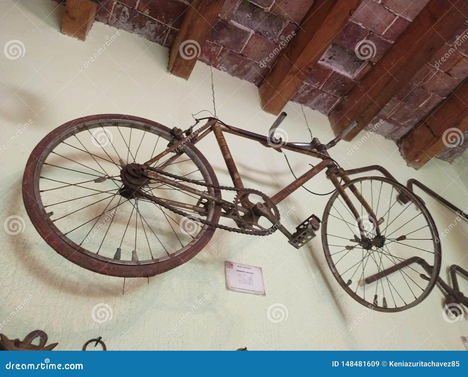 Een oude fiets die op de muur hangen