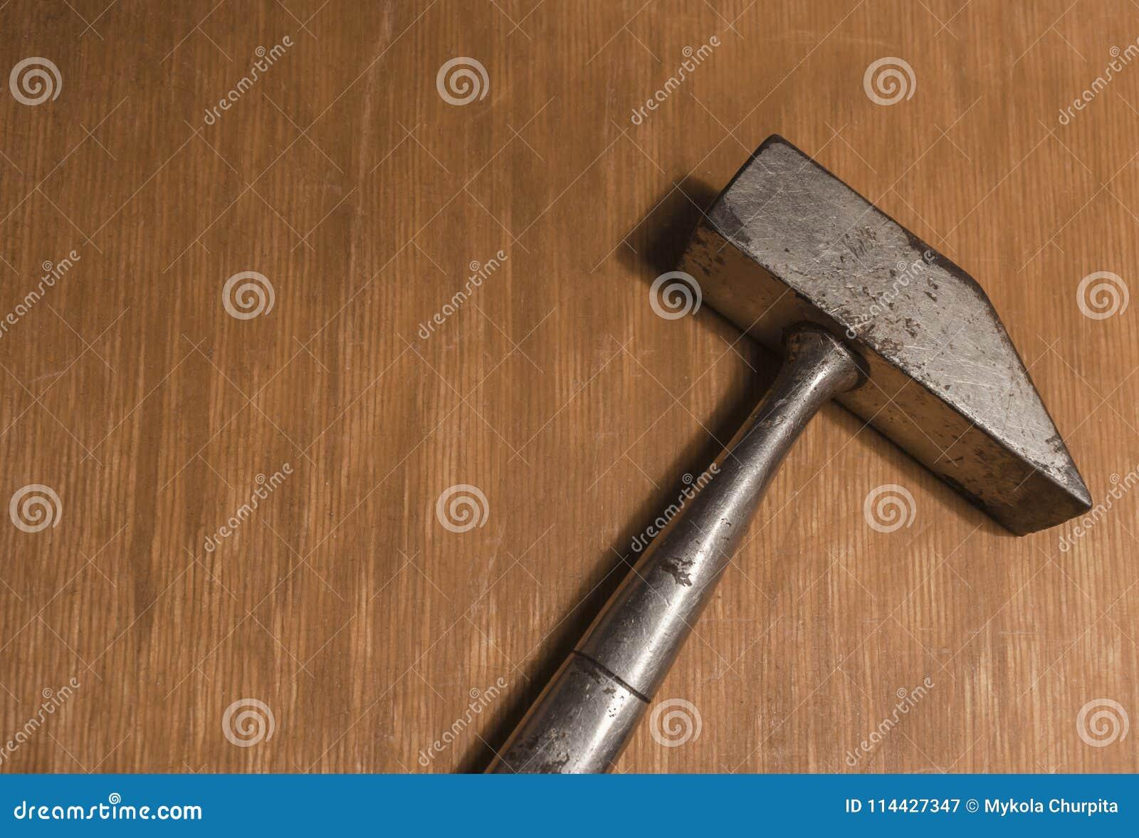 Een oude hamer op een houten oppervlakte